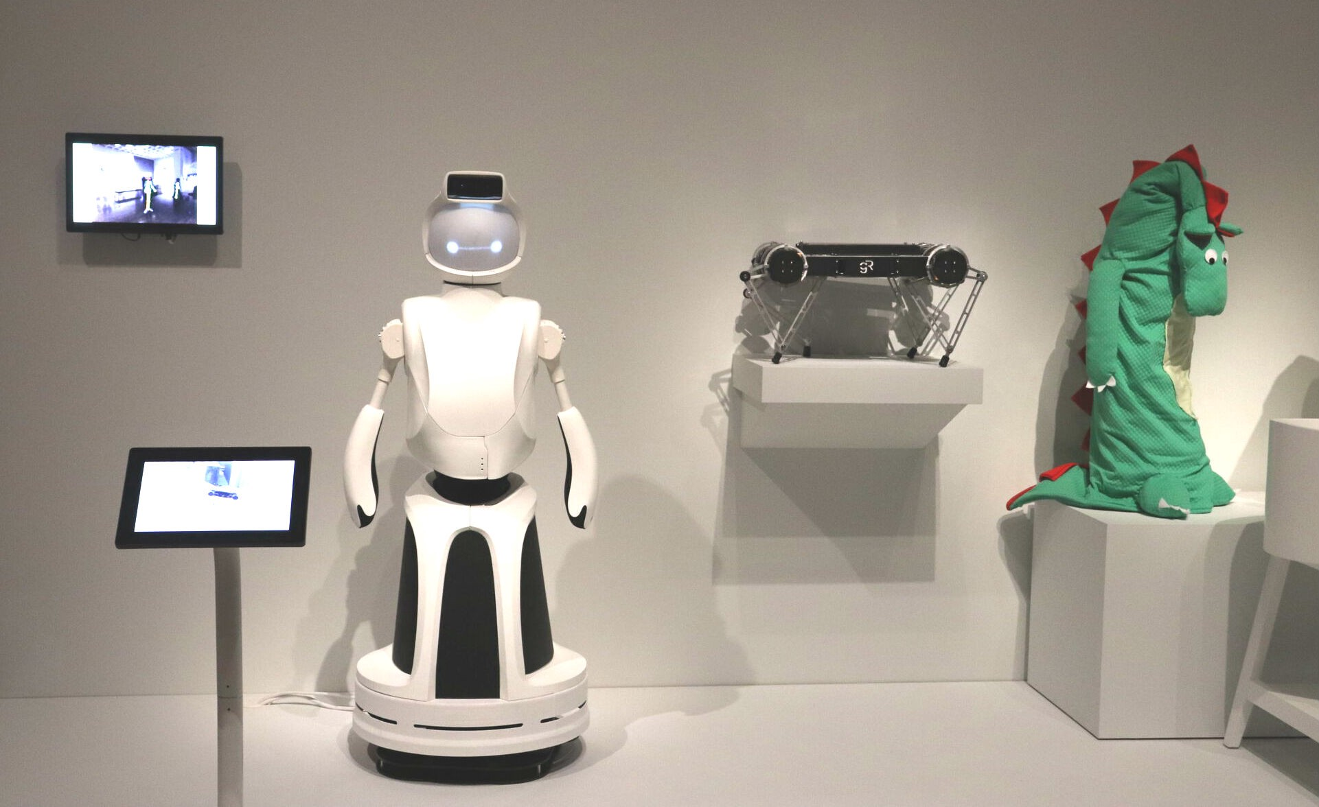 Three different robots in museum exhibit, one is human-shaped, one is a flat block with legs, last is wearing a dino costume