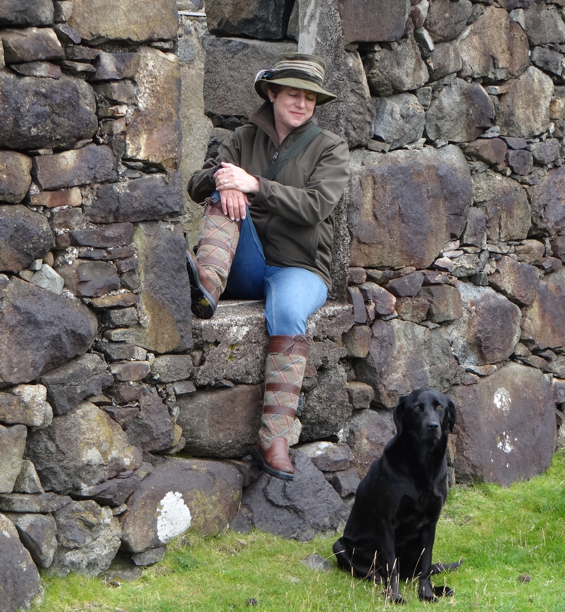 Image of the author a woman in country coat and hat sat in window opening of a ruined building. Her black dog sat on ground