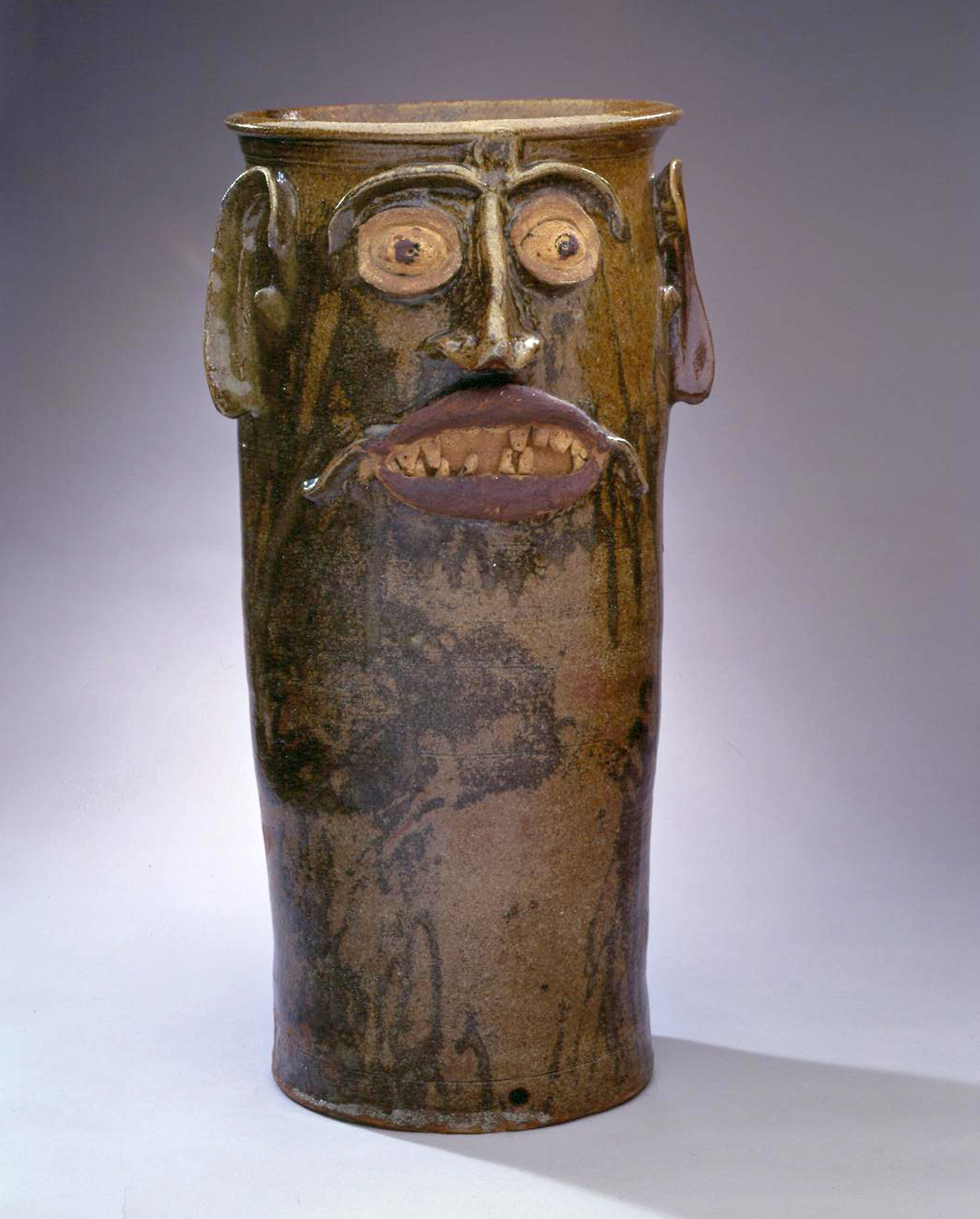 Tall brown face jar with a toothy grimace.