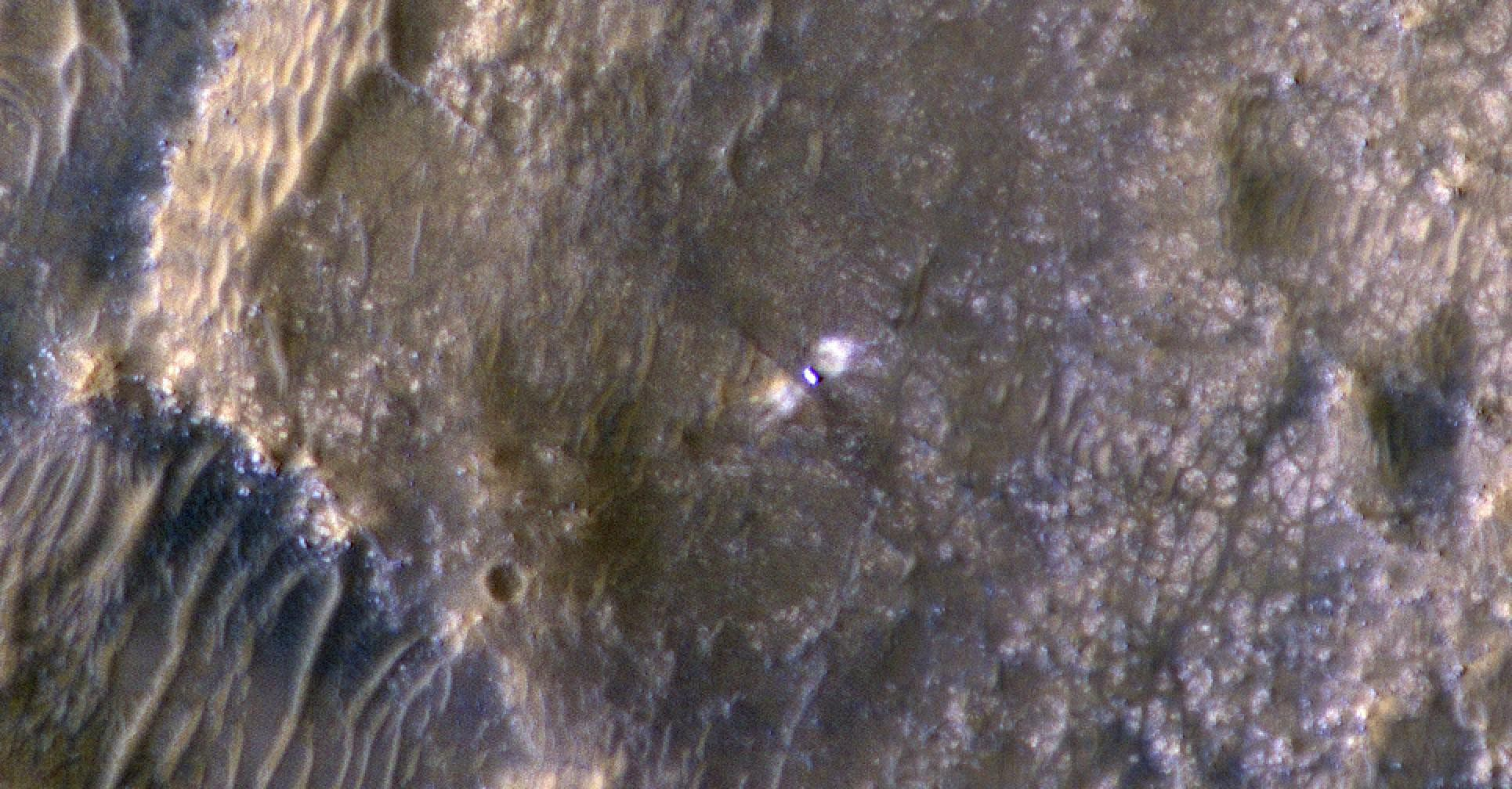 The High-Resolution Science Experiment (HiRISE) camera aboard NASA's Mars Reconnaissance Orbiter (MRO) took this image of the Perseverance rover on Feb. 24, 2021. The false-color image shows a ring of blast marks where thrusters from the rover's descent stage blew away dust during landing on Feb. 18, 2021.