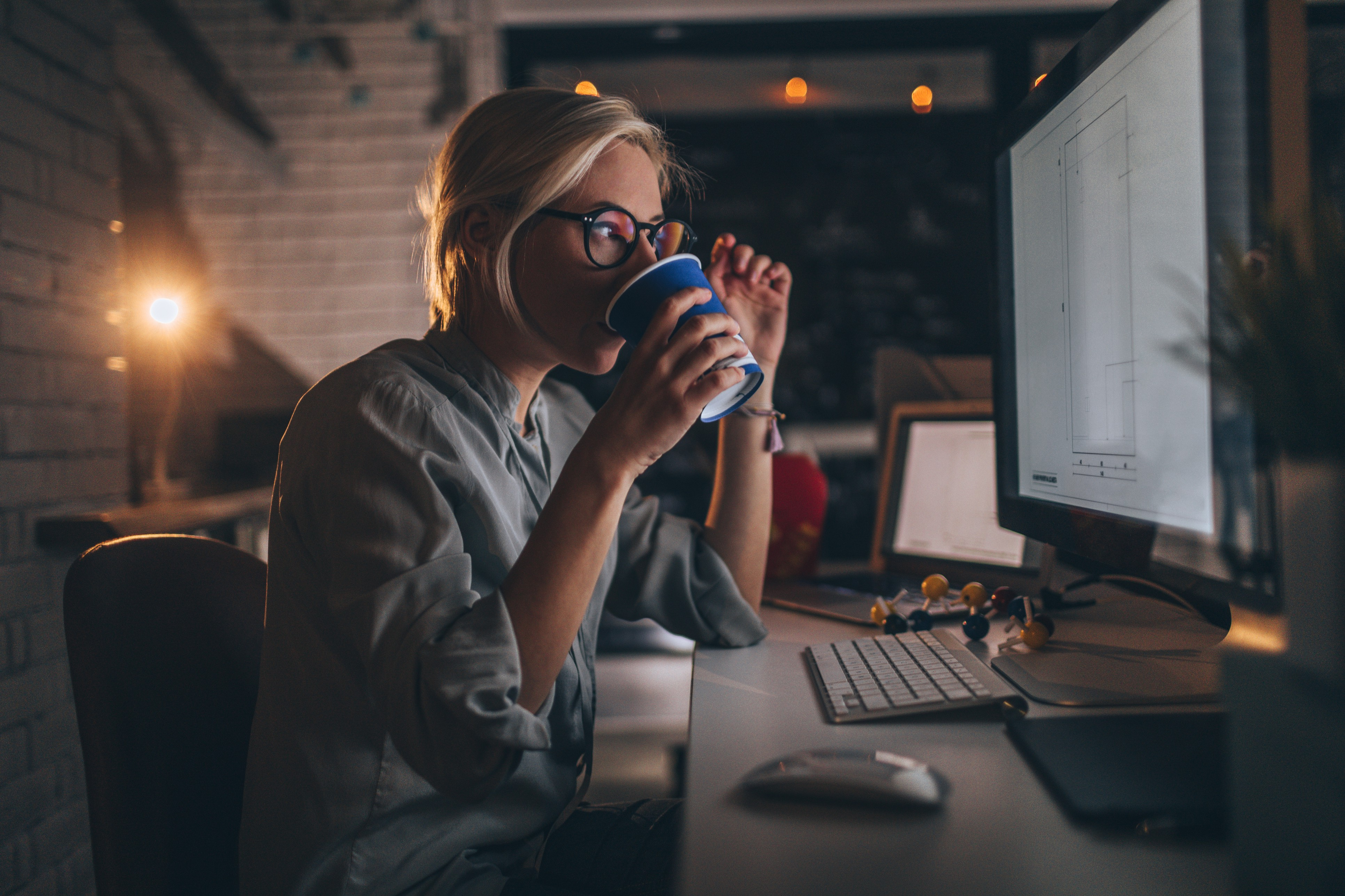 Woman sipping coffee at computer screen.