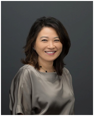A professional photo of Carol Choi smiling in front of a grey background