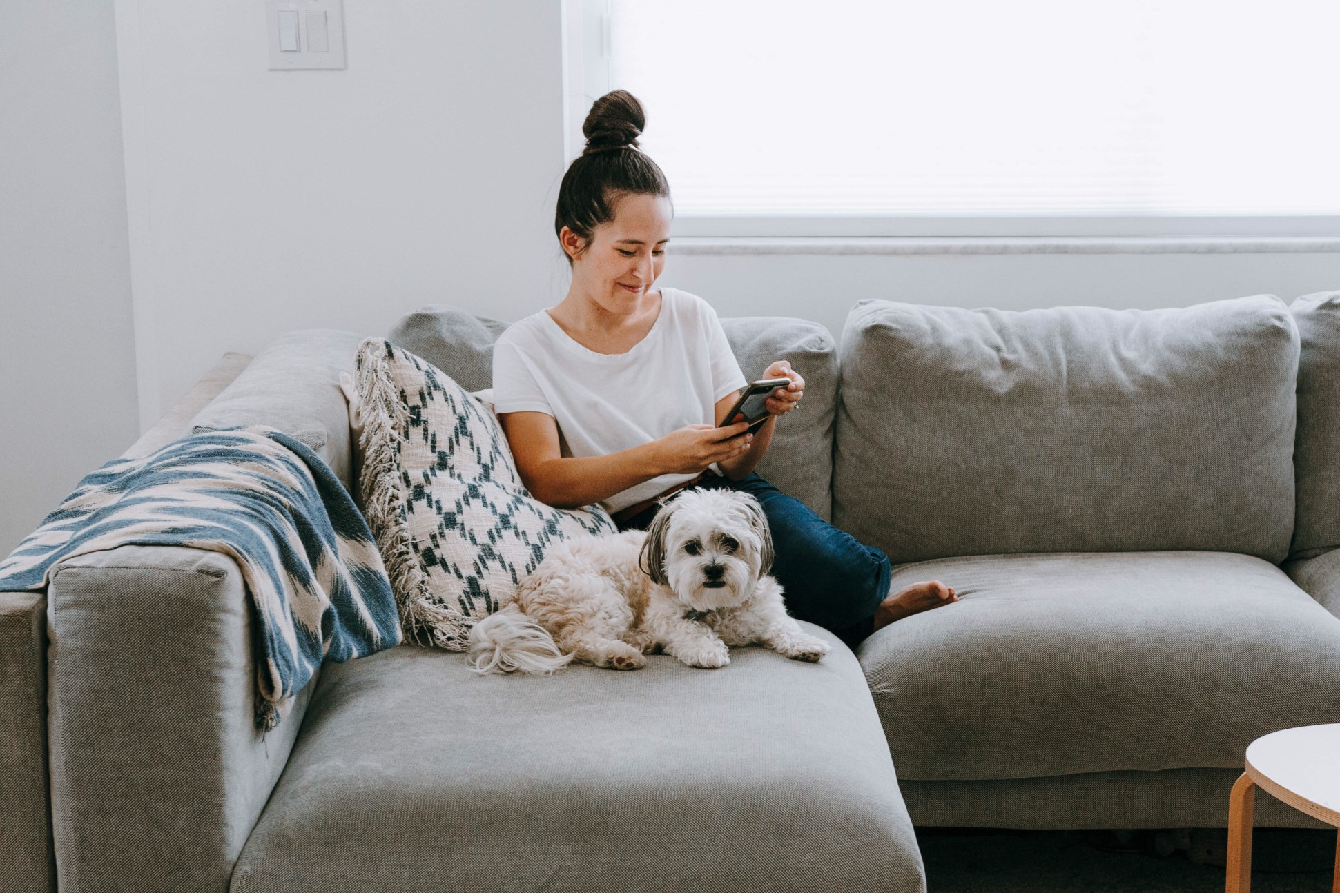 A woman smiles while looking at her phone and sitting next to her dog on the couch.