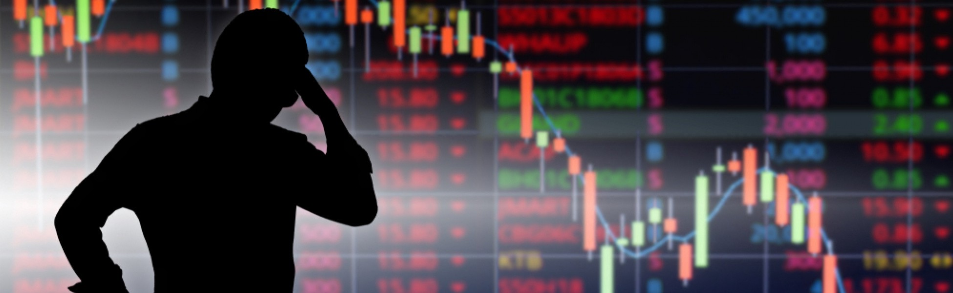 A Wall Street trader looks at a monitor showing the stock market index going down because of the coronavirus pandemic