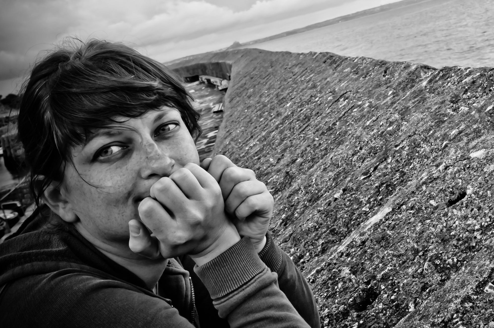 Portrait of me leaning on a sea wall with St Michael's Mount, Cornwall in the distance. My eyebrows have bald patches.