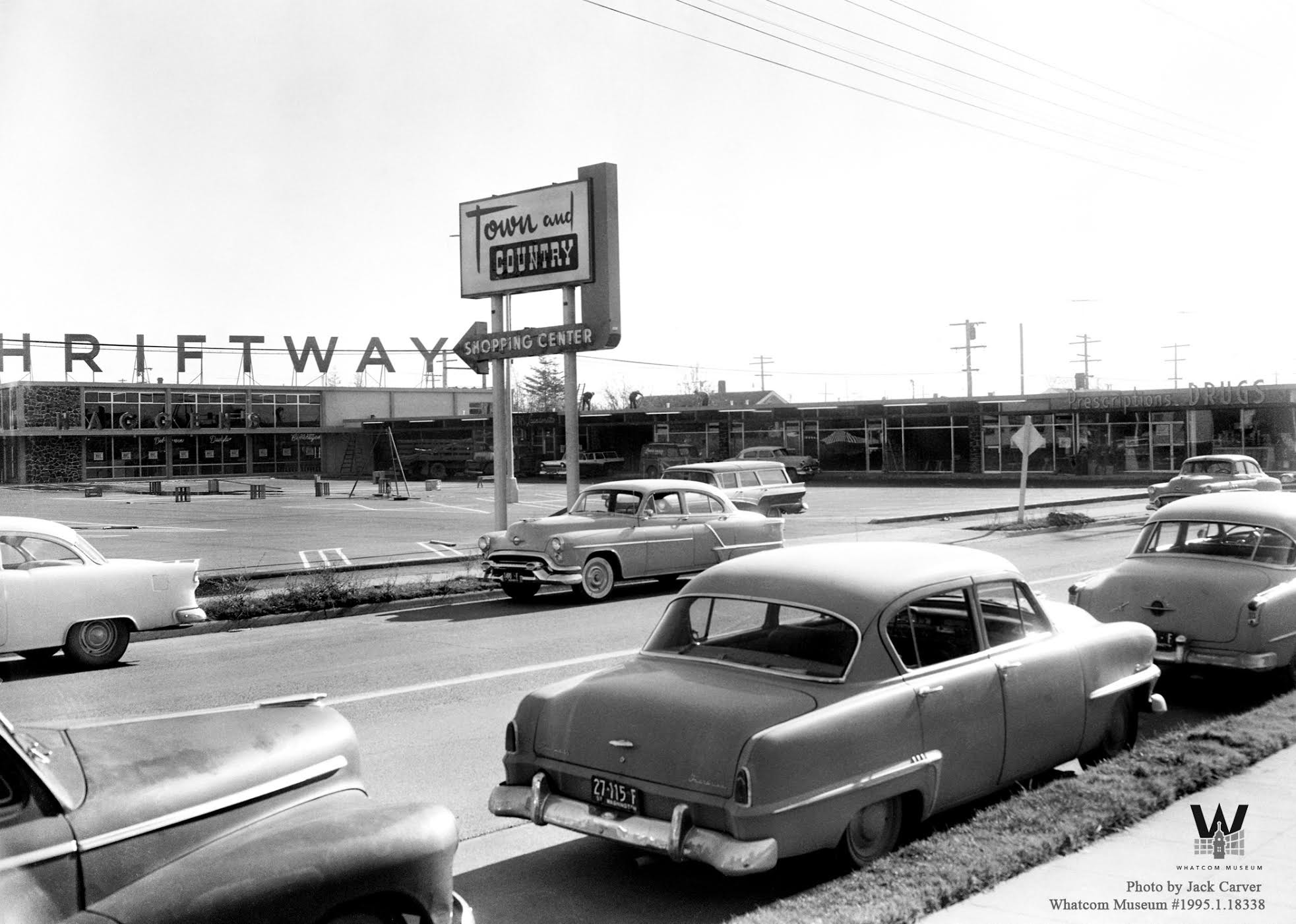 black and white image of shopping center with cars in the foreground