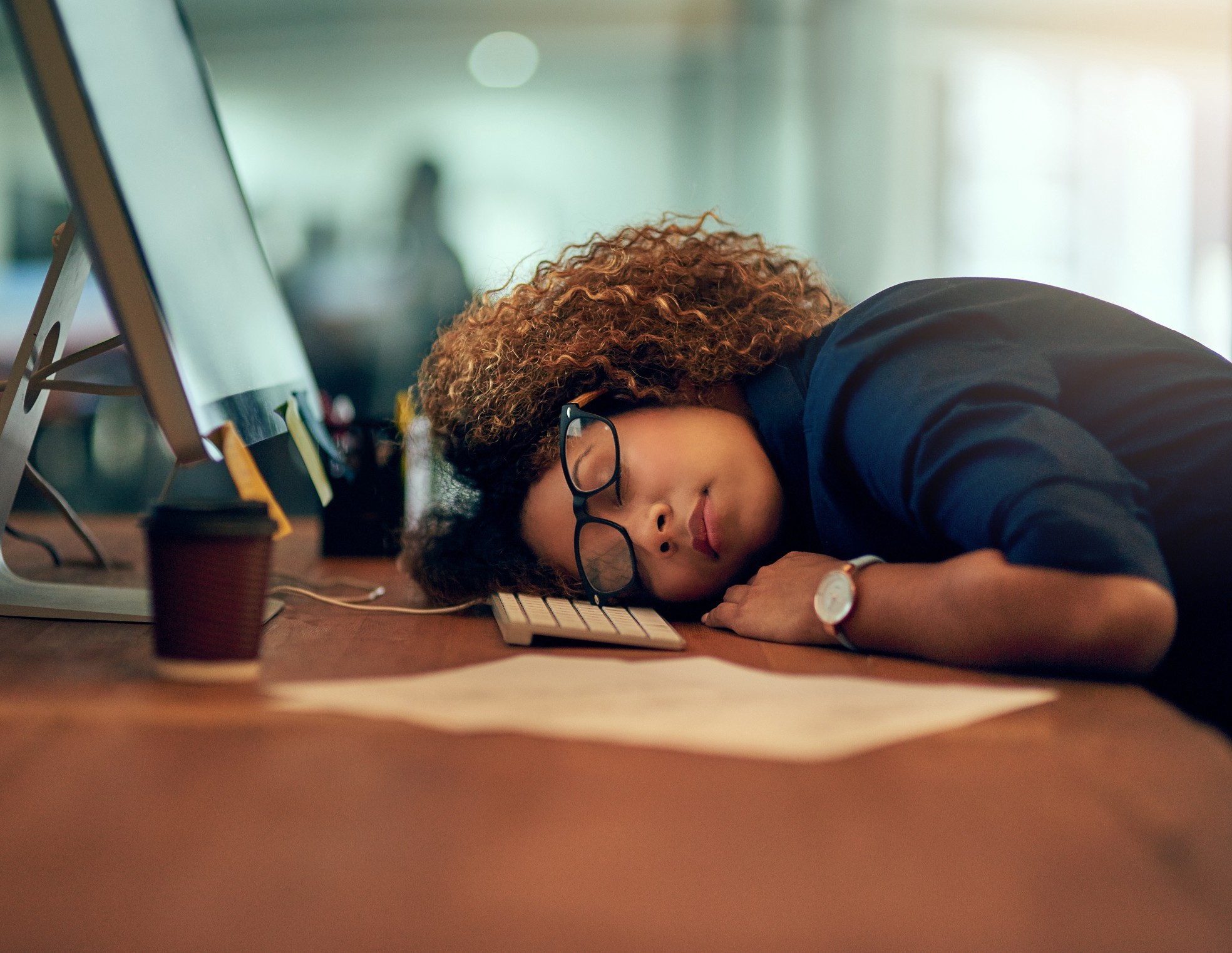 Exhausted Black businesswoman sleeping at her desk.