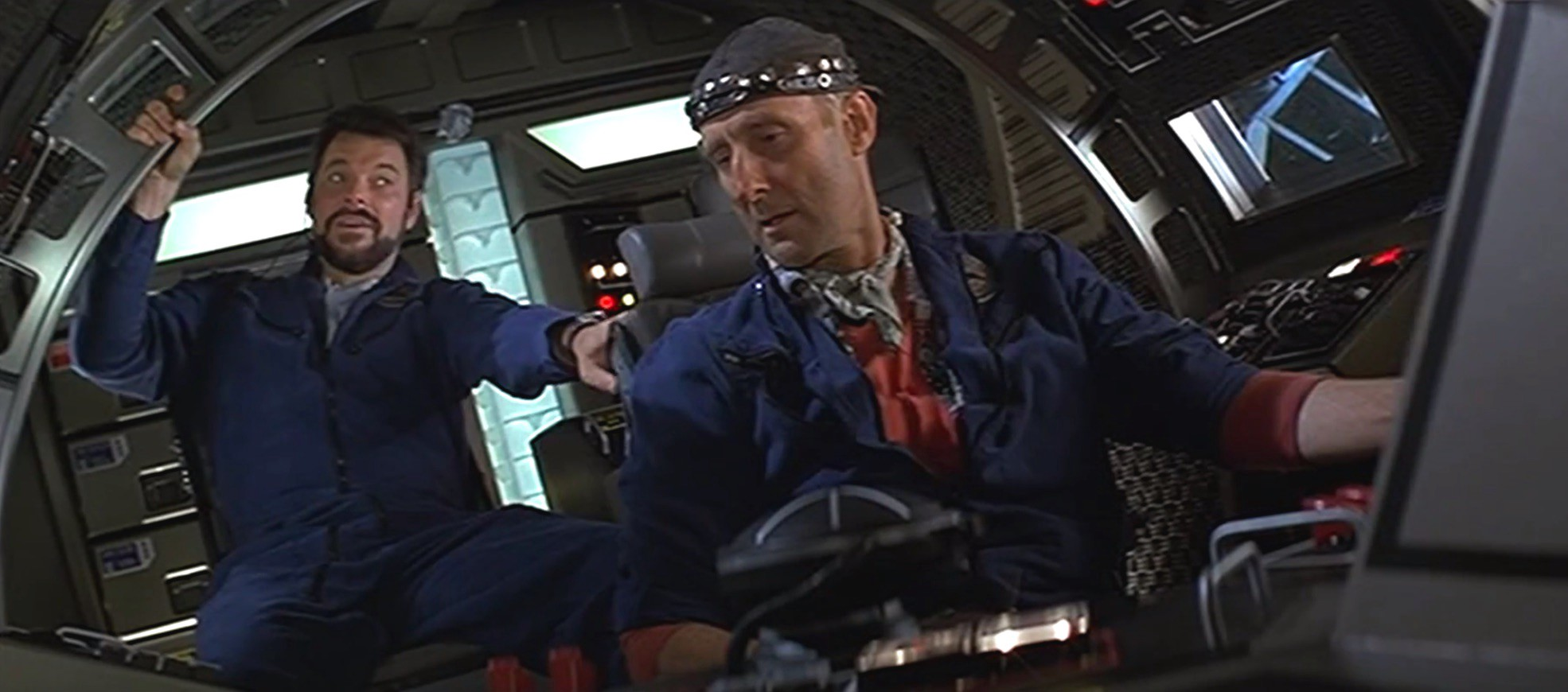 Two men talking to each other in the cockpit of a rocket ship, from Paramount Pictures' 1996 film Star Trek: First Contact