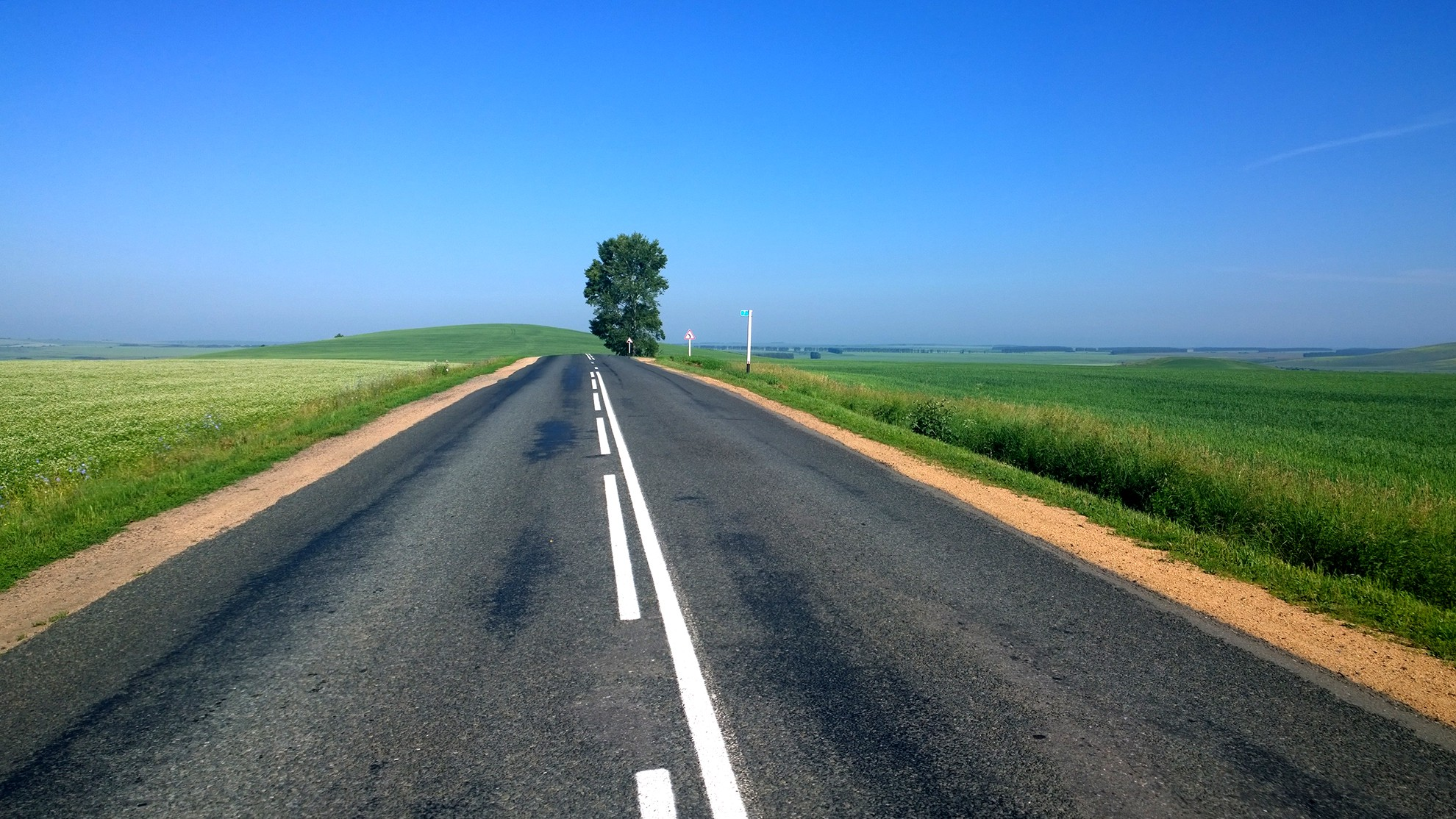 A stretch of a long, empty road against a blue sky.