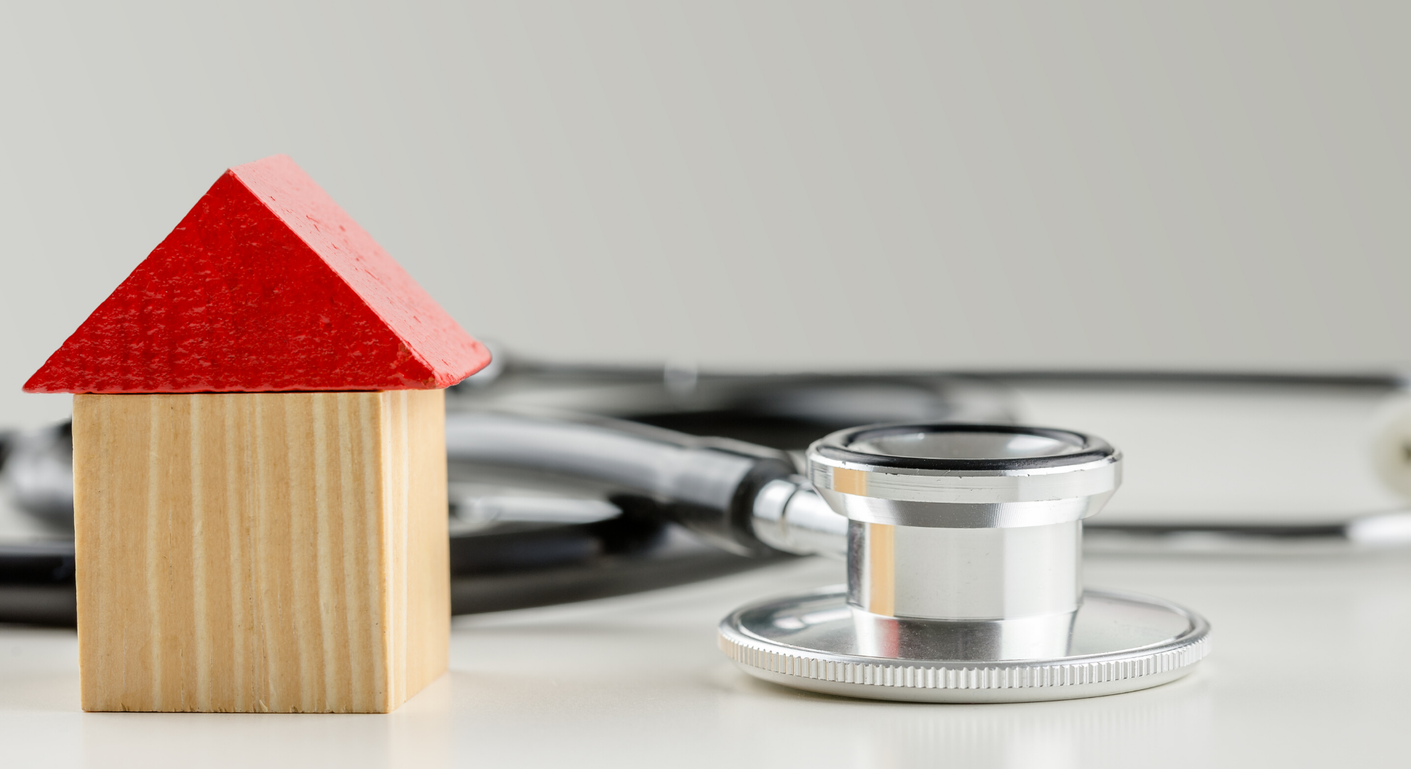 Wooden toy house next to a stethoscope. Conceptual image of solution to the real estate market crisis.