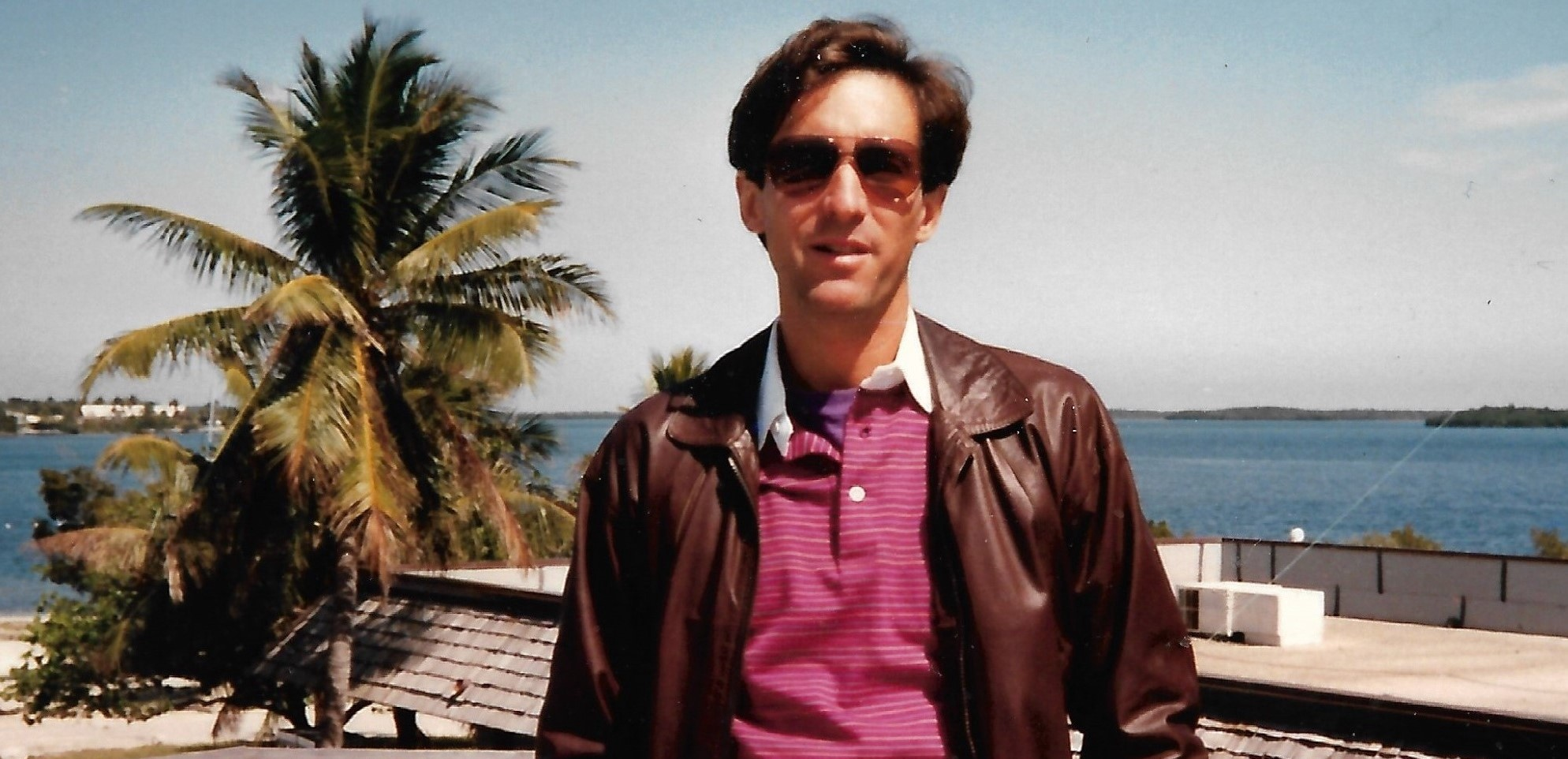 Vintage photo of a light-skinned man with brown hair, wearing aviator shades, a leather jacket, and a polo t-shirt, standing in front of a palm tree and the ocean.