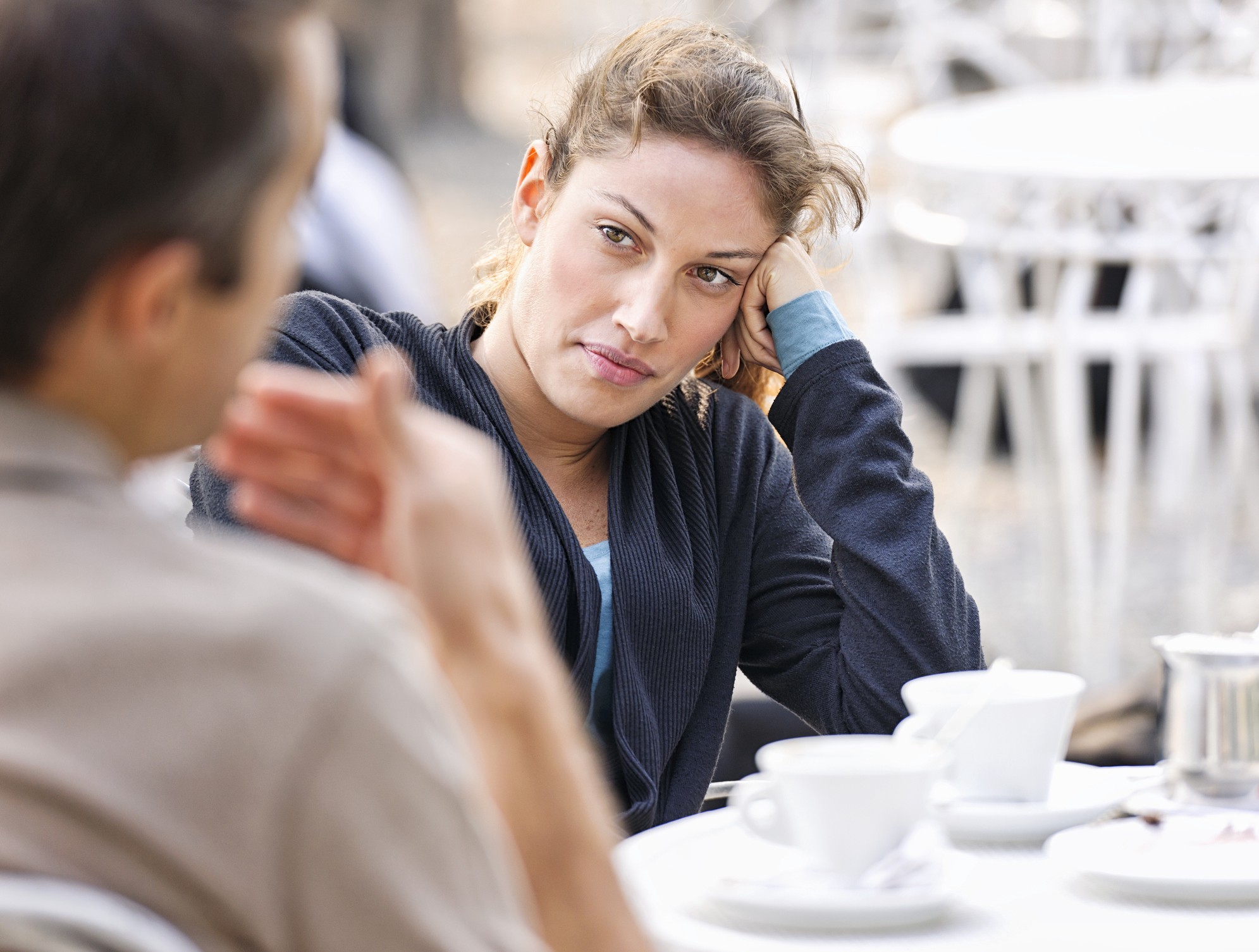 A photo of a slightly disgruntled woman looking at a man talk, waiting for him to finish.