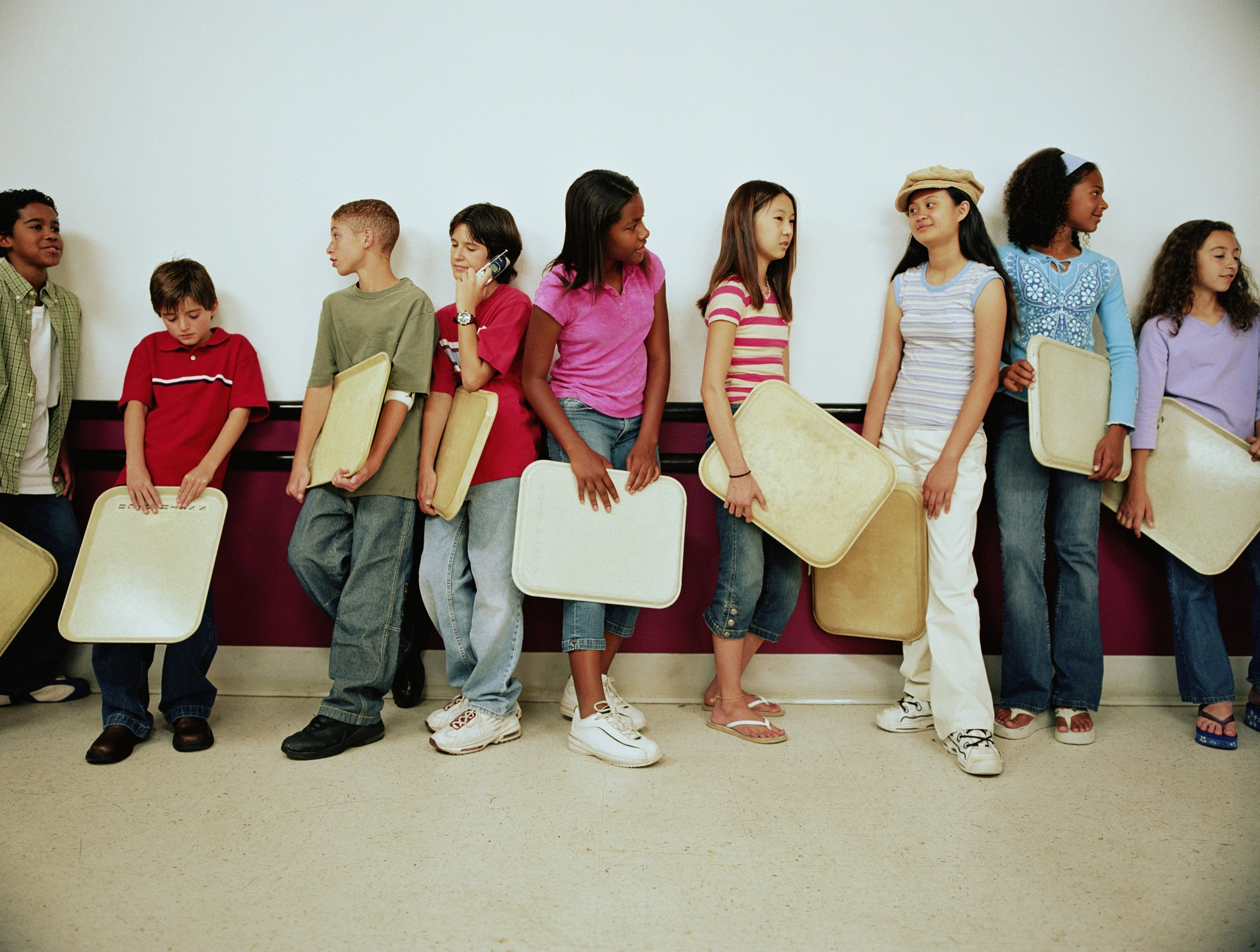 Middle school kids holding their trays wait in a school lunch line.