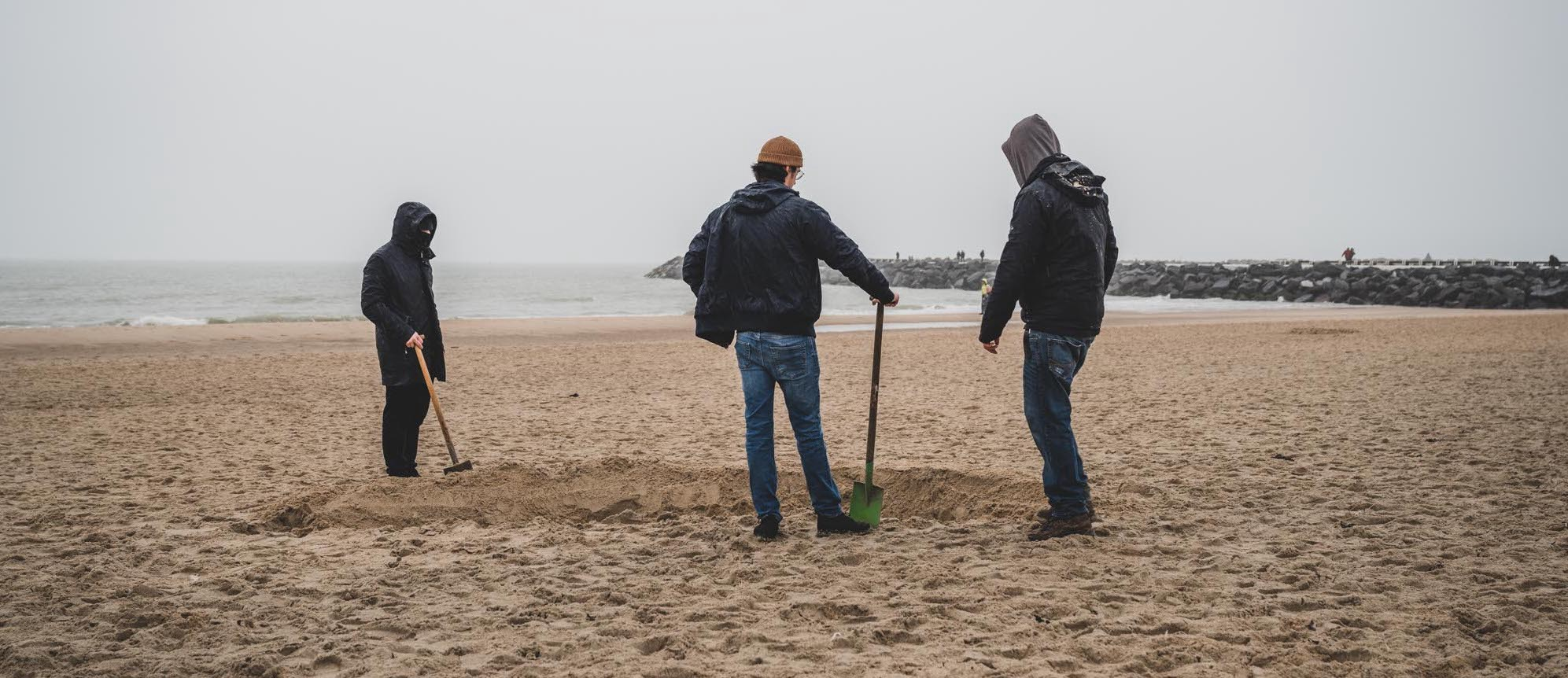 Three men building a sandcastle, or rather discussing it
