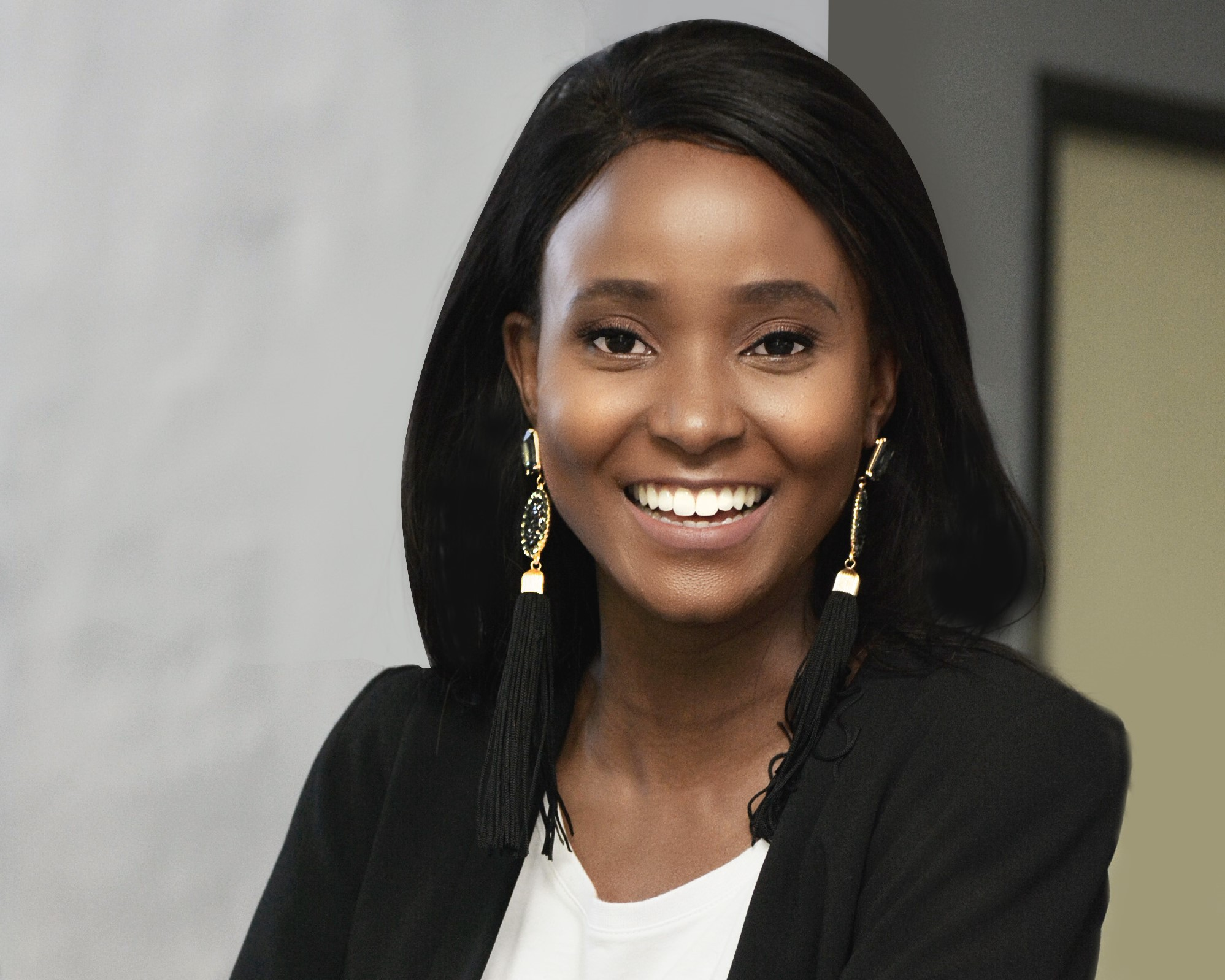 A young woman from Botswana smiles at the camera, with her arms folded. She wears a black blazer and white T-shirt.