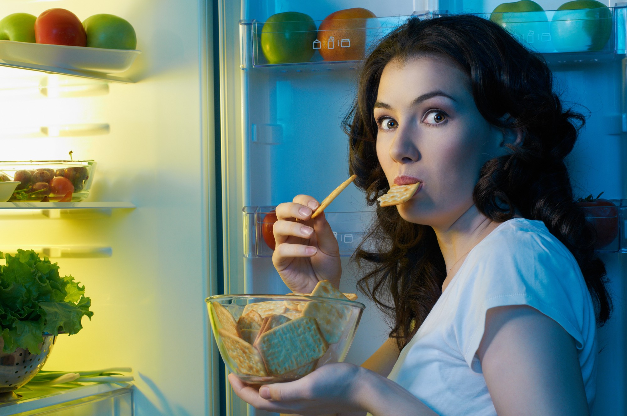 girl with long dark hair wearing white t-shirt eating food in front of refrigerator