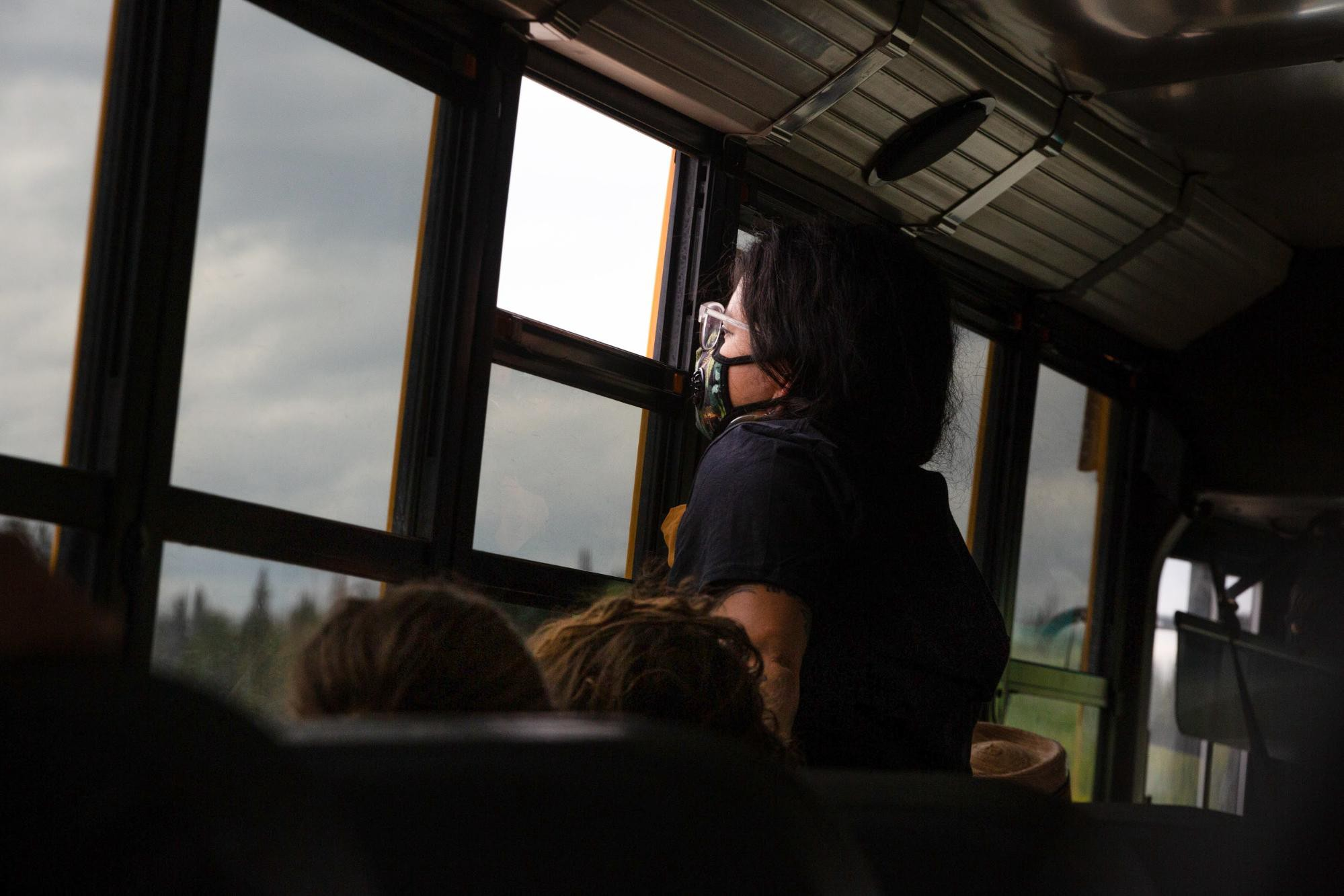 V Guzman looks outside at a Syncrude refinery with a mask against the foul odors from the local tar sands mining facilities.