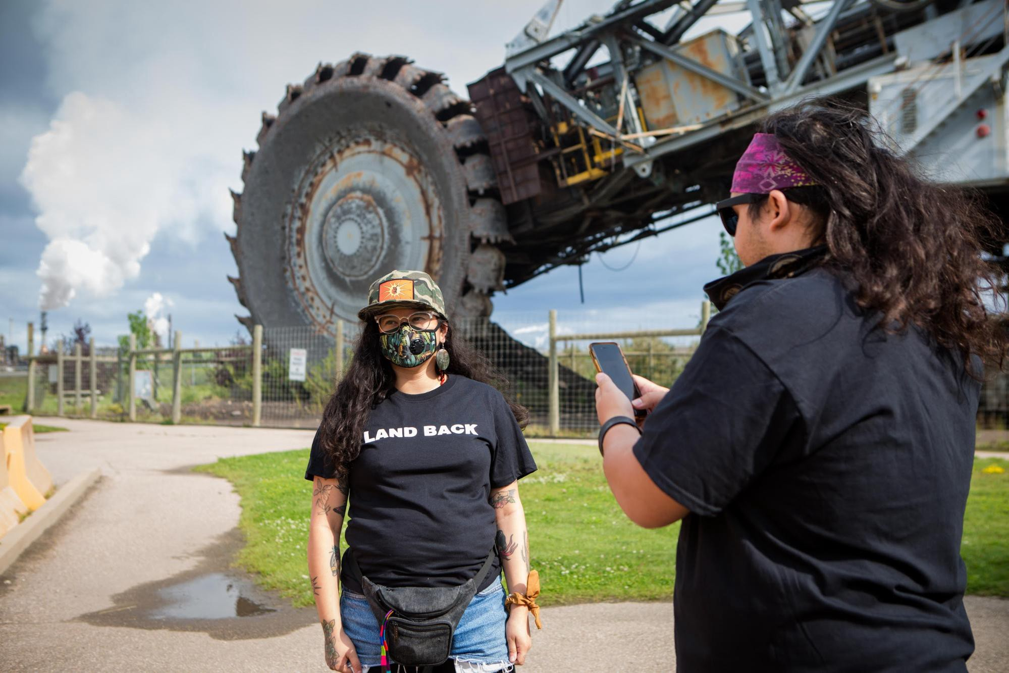 V Guzman poses outside a Suncor tar sands facility against massive machinery to demonstrate the scale of the extraction.