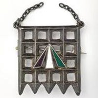 A brooch shaped like a prison door with green, white, and violet detailing