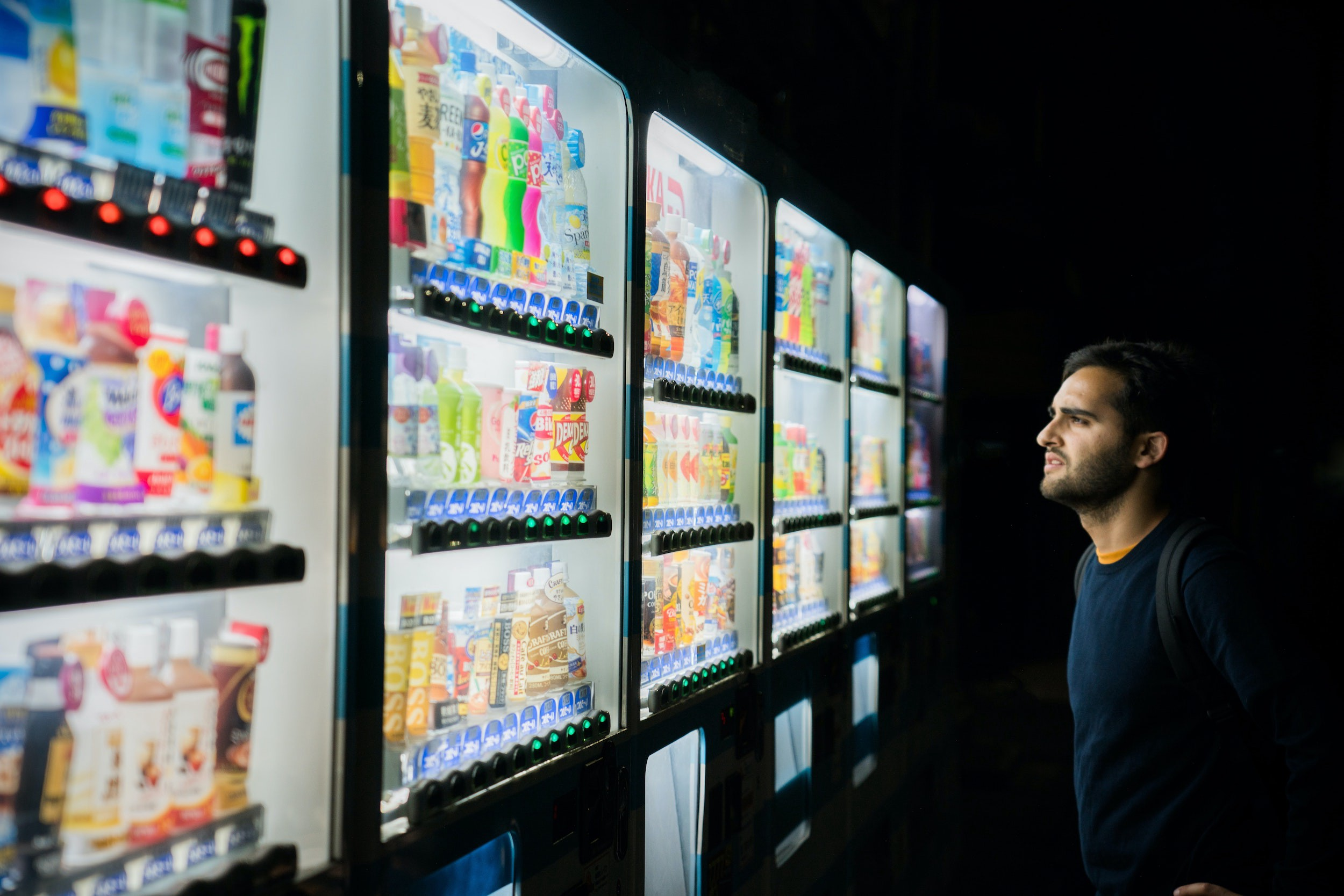Man stares at choices in multiple vending machines.