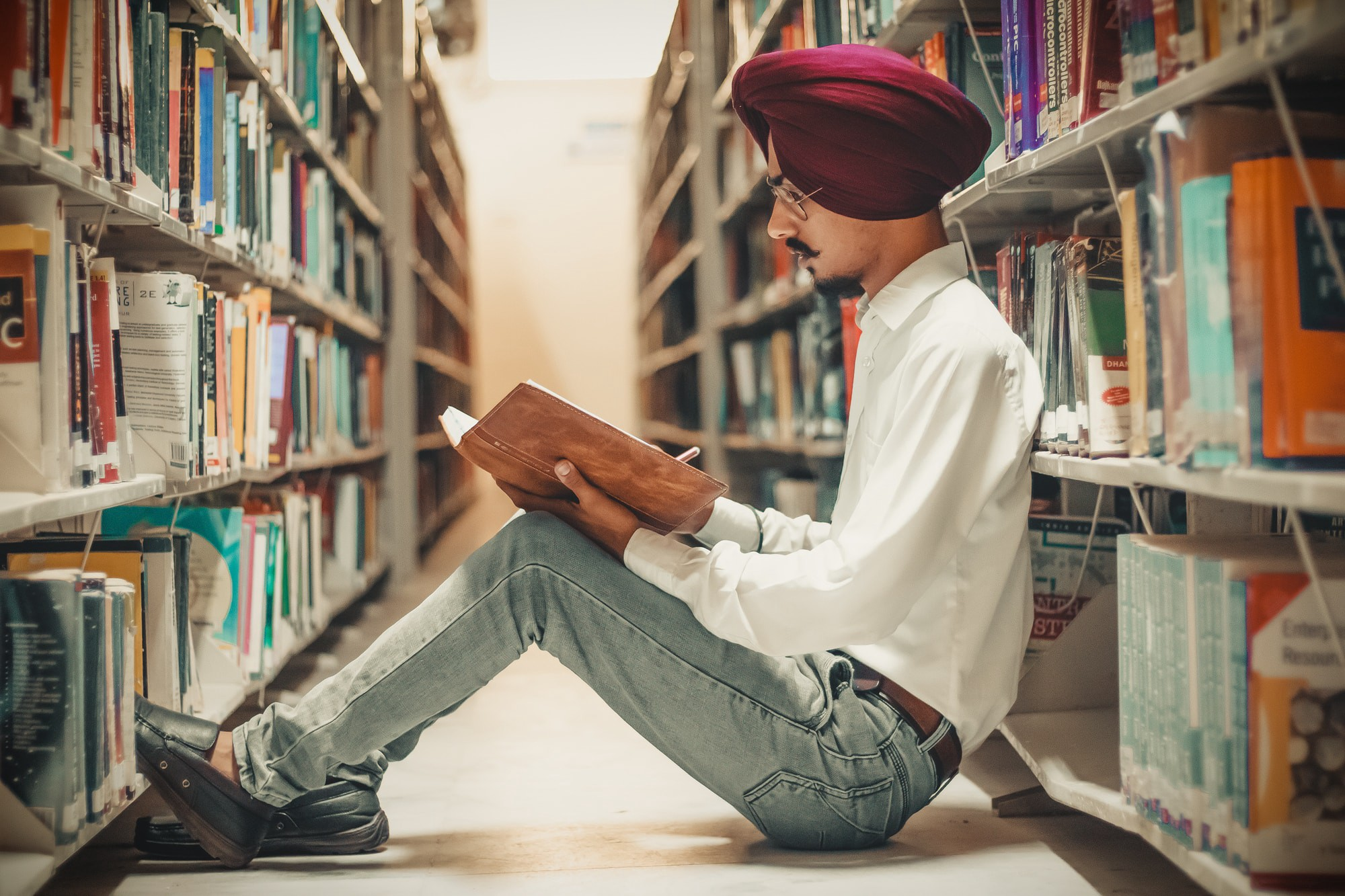 Managing College Stress: Young man wearing turban studying while seated in a library aisle