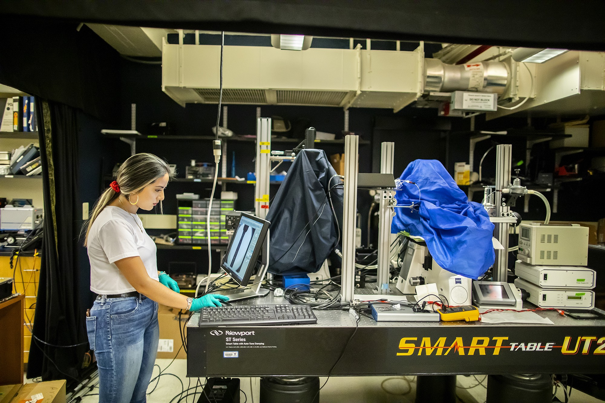 Angelica Padilla works at a computer station on a lab bench piled with electronic equipment.