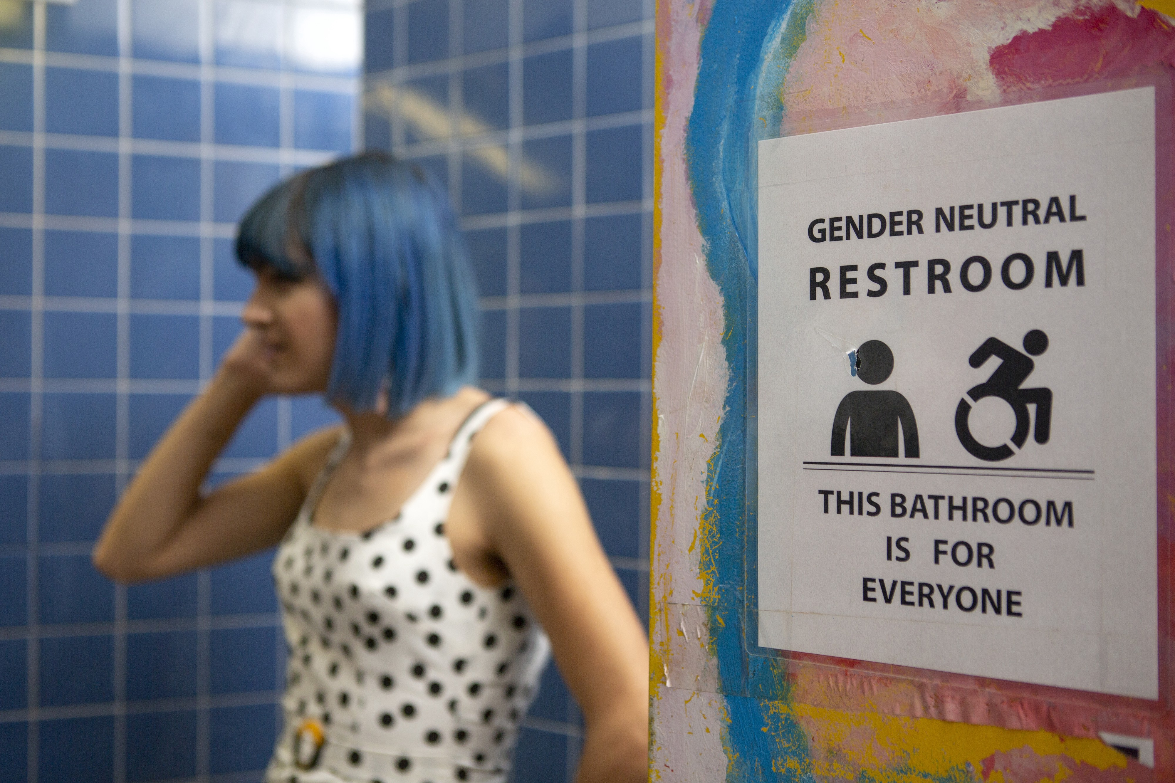 """This picture of a white-passing non-binary person standing in a restroom next to a sign that reads """"Gender Neutral Restroom."""