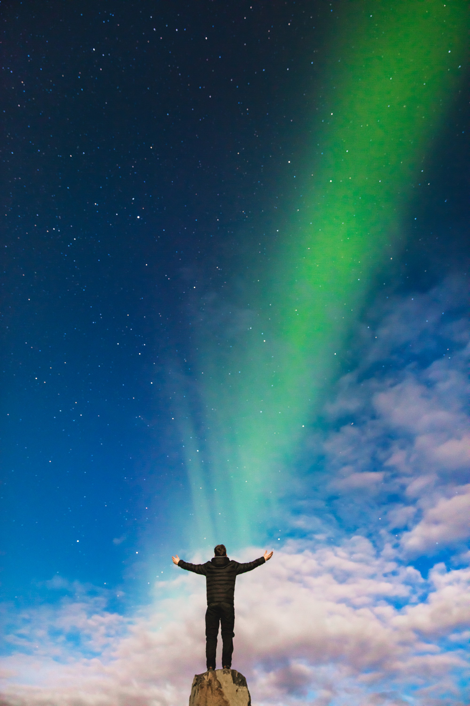 A man standing on a rock under the northern lights with the sun setting (or perhaps rising)