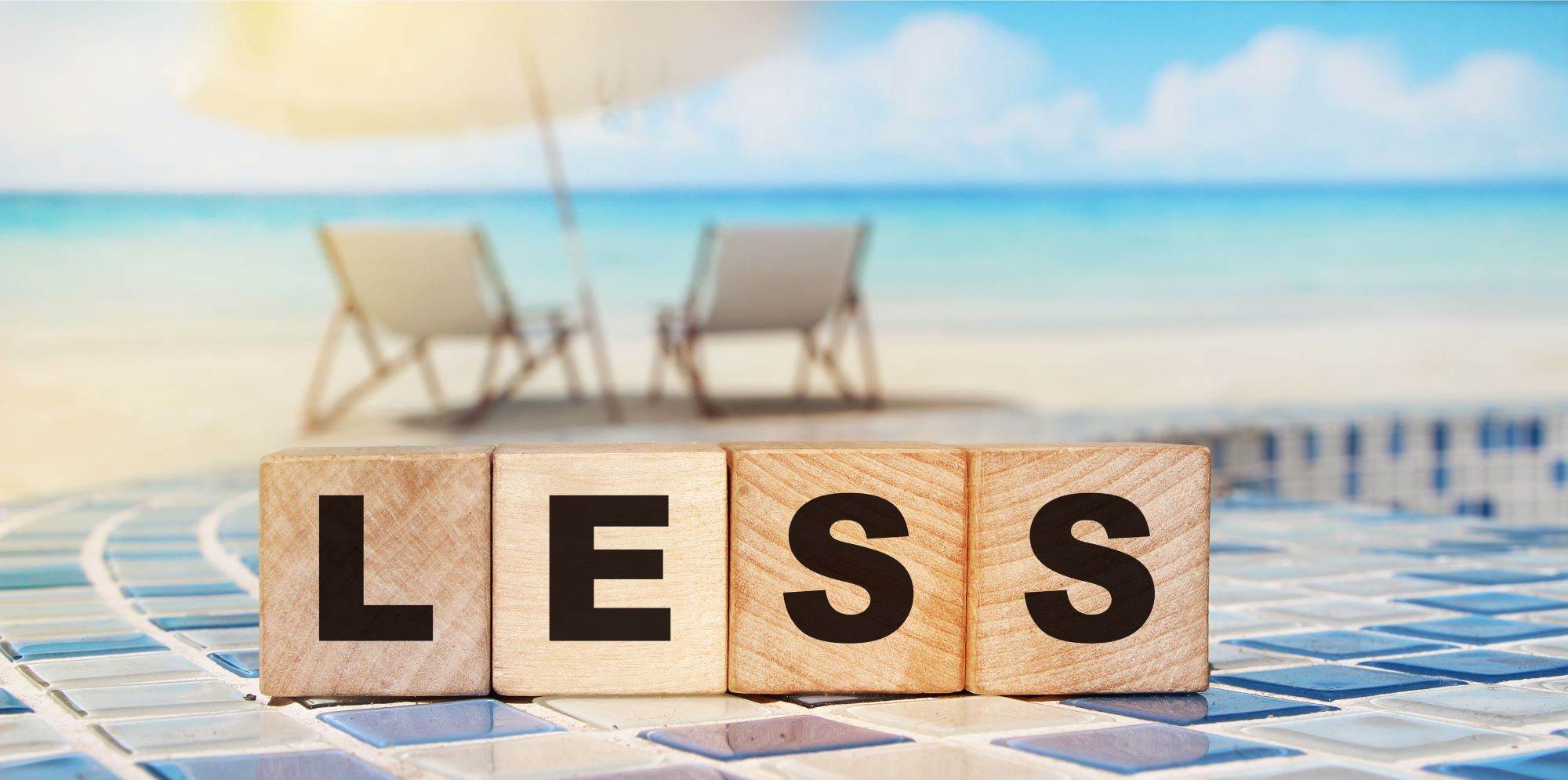 """Scrabble blocks that say """"less"""" in front of a beautiful beach"""