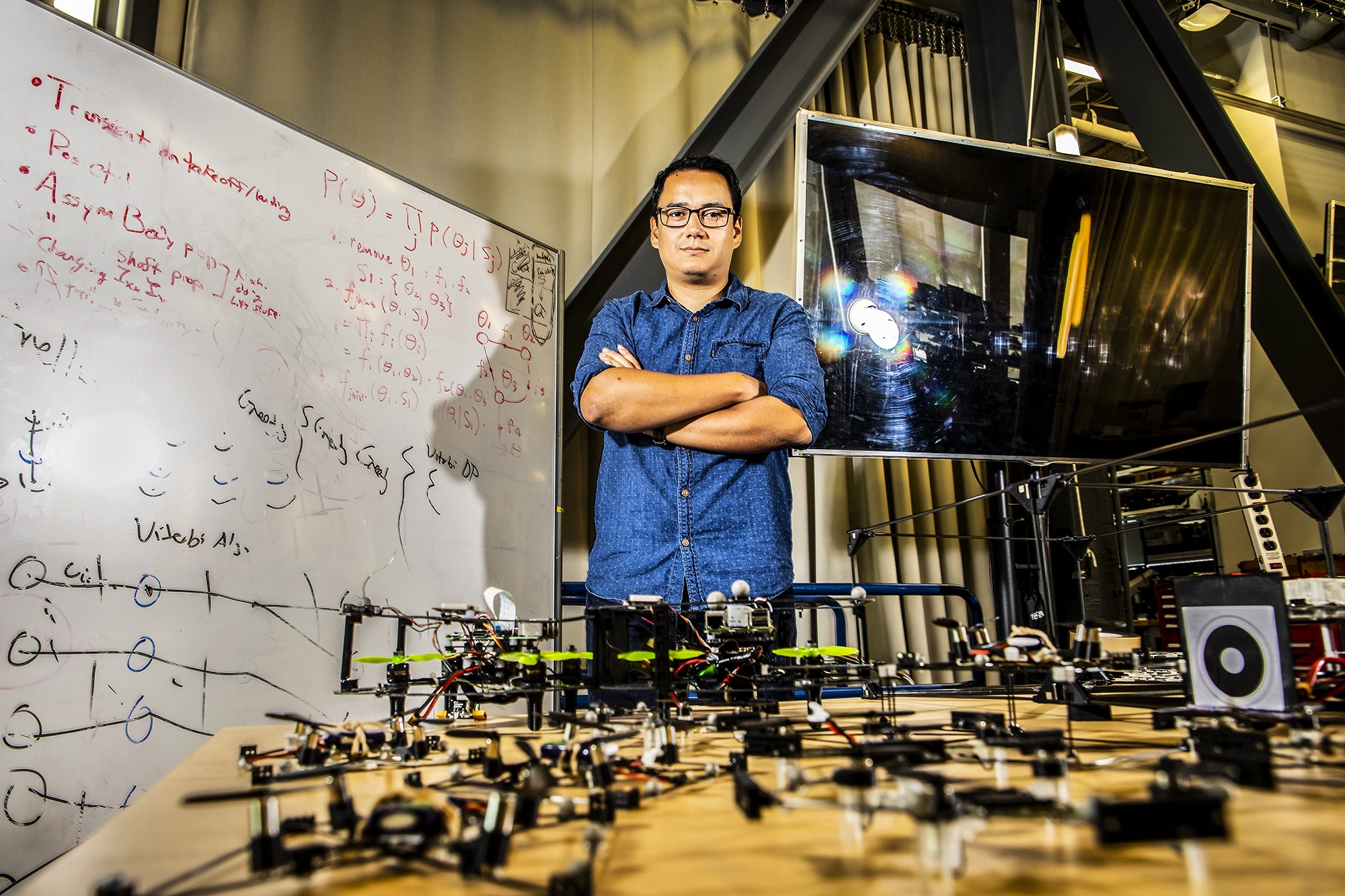 Postdoctoral researcher David Saldaña poses in front of a fleet of small flying robots.