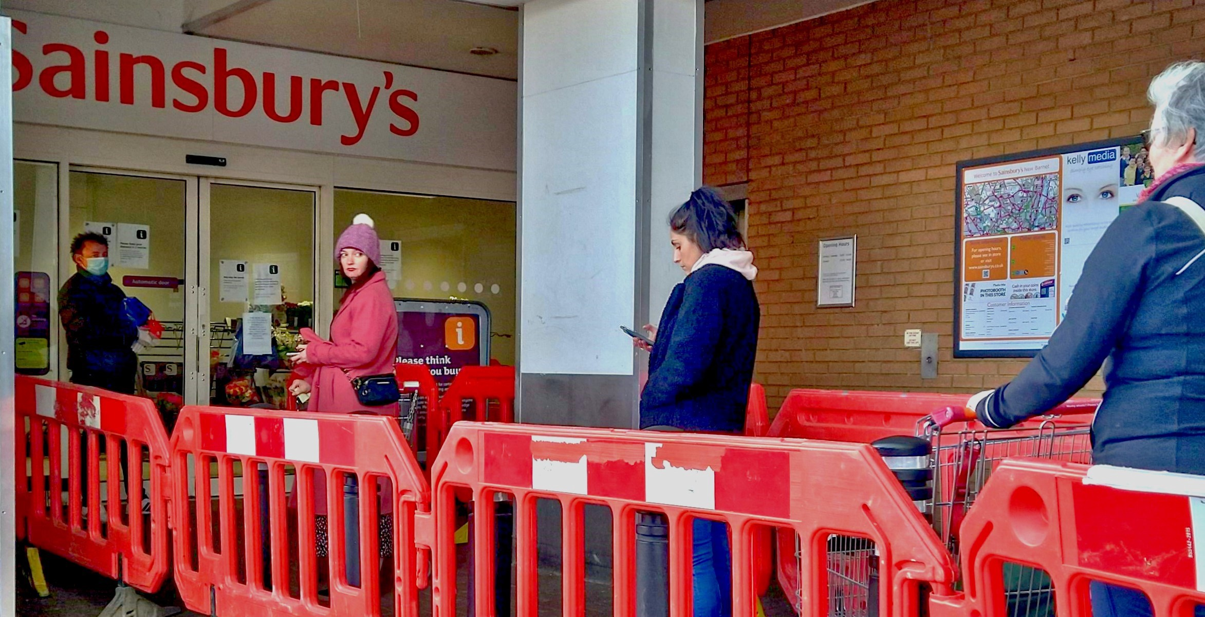 Socially-distant shoppers queueing for a Sainsbury's.