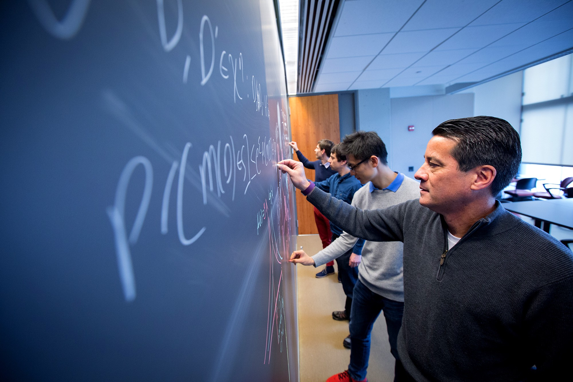 Four researchers write equations on a chalkboard.