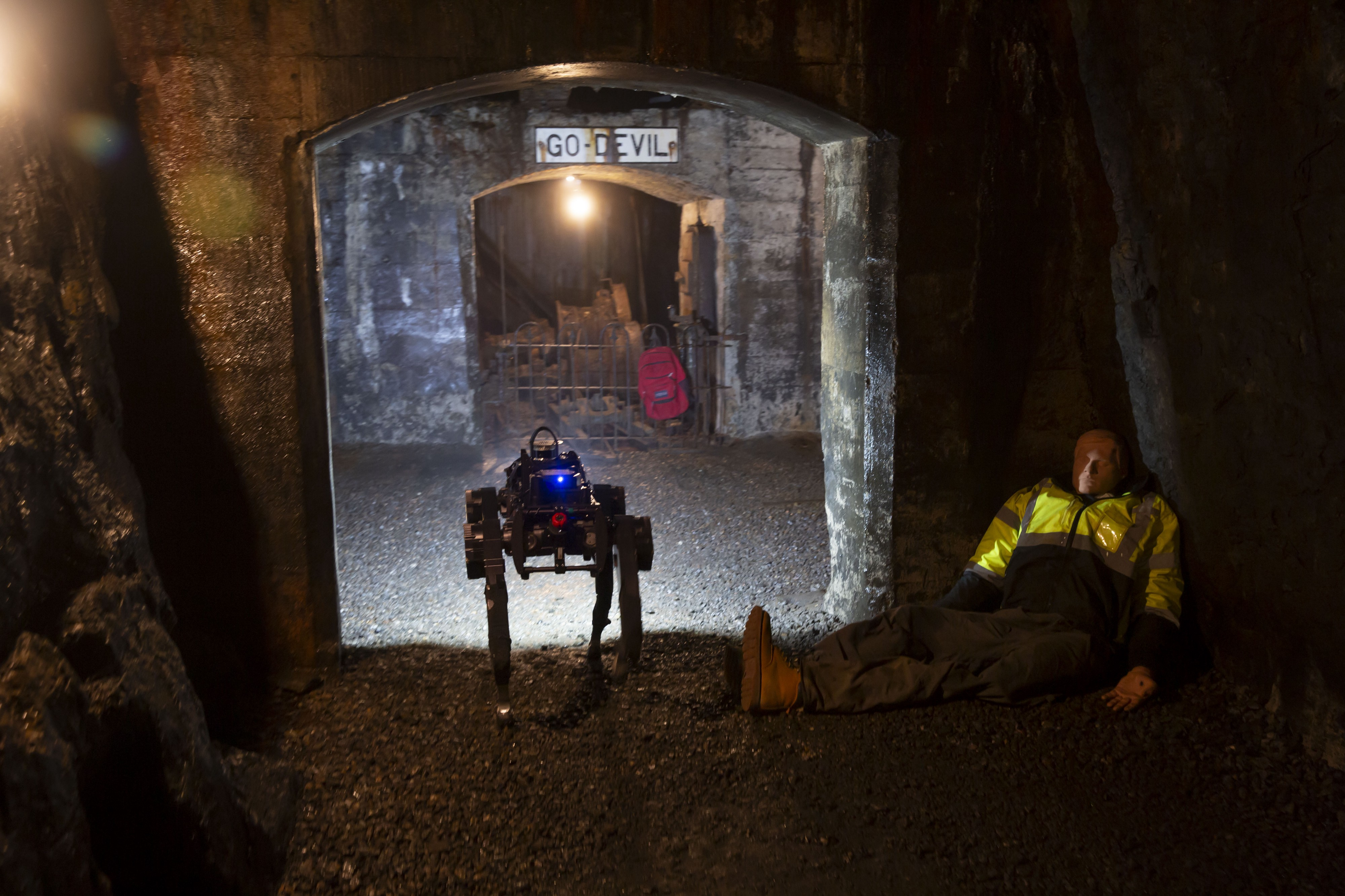 In a dimly lit tunnel, a dog-like legged robot walks past a mannequin posing as a mine-worker in need of rescue.