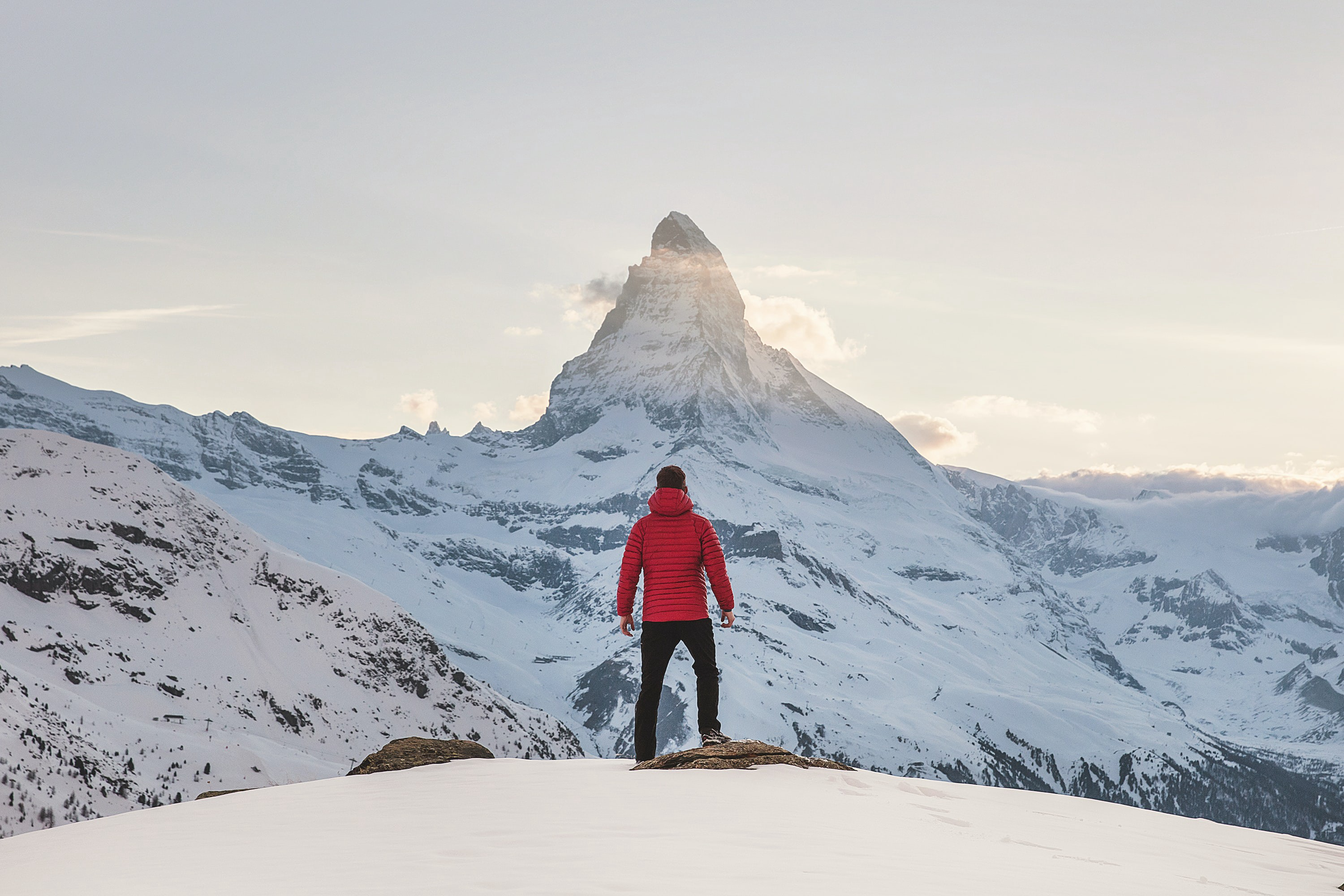 A man in a puffy, red jacket stands on a snowboard facing a mountain in the background.