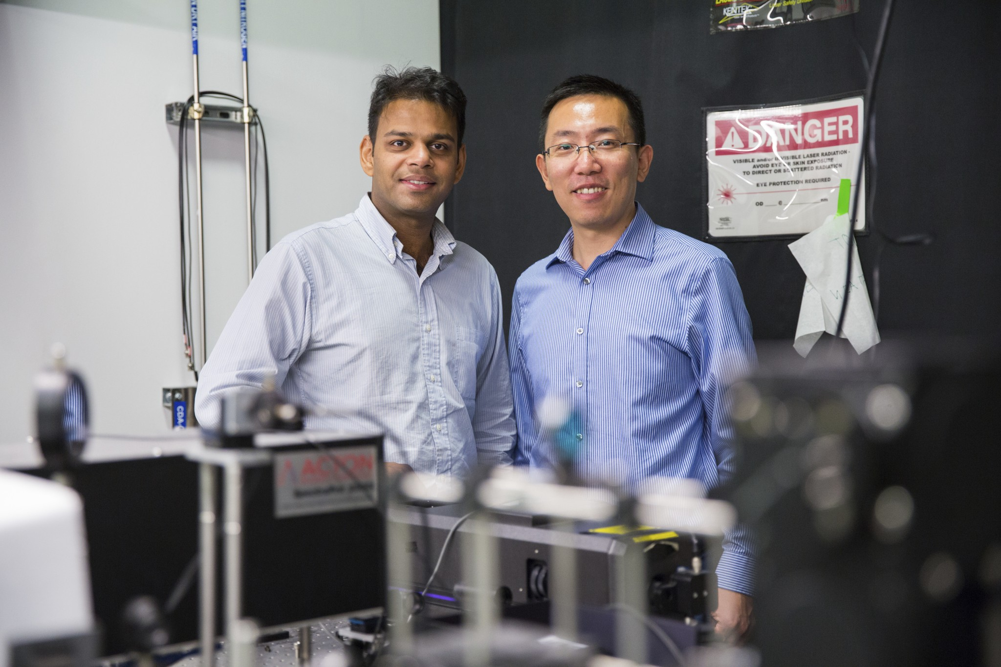 Ritesh Agarwal and Liang Feng pose among electrical engineering equipment.