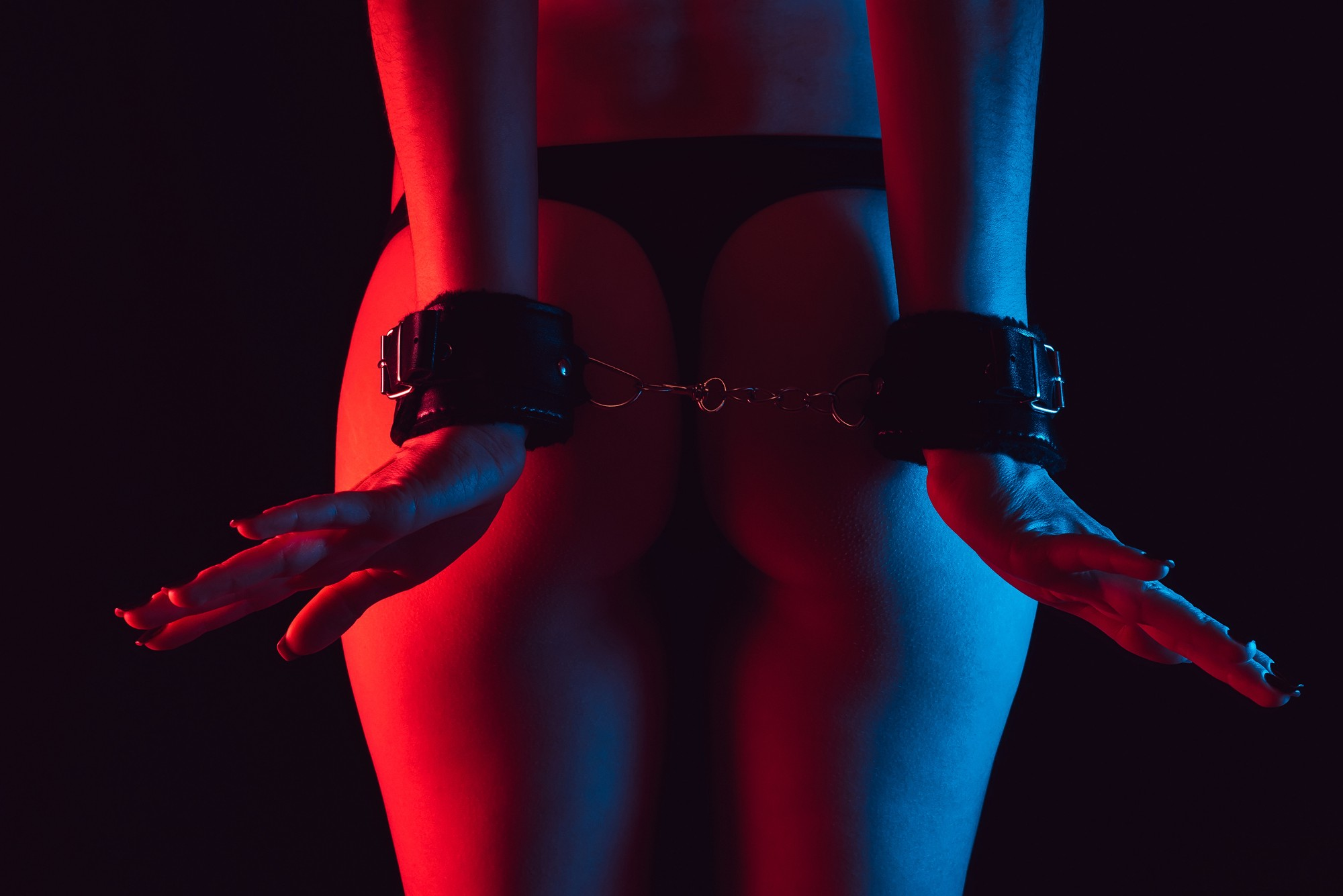 Woman handcuffed with her wrists behind her back showing her naked bum