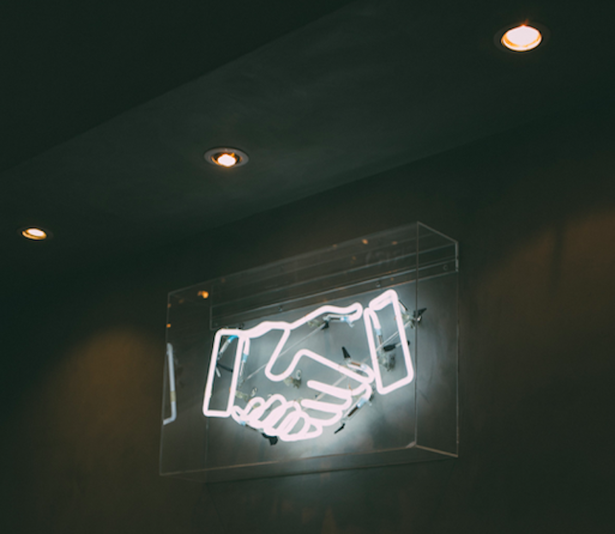 A neon art piece of a handshake between two hands.