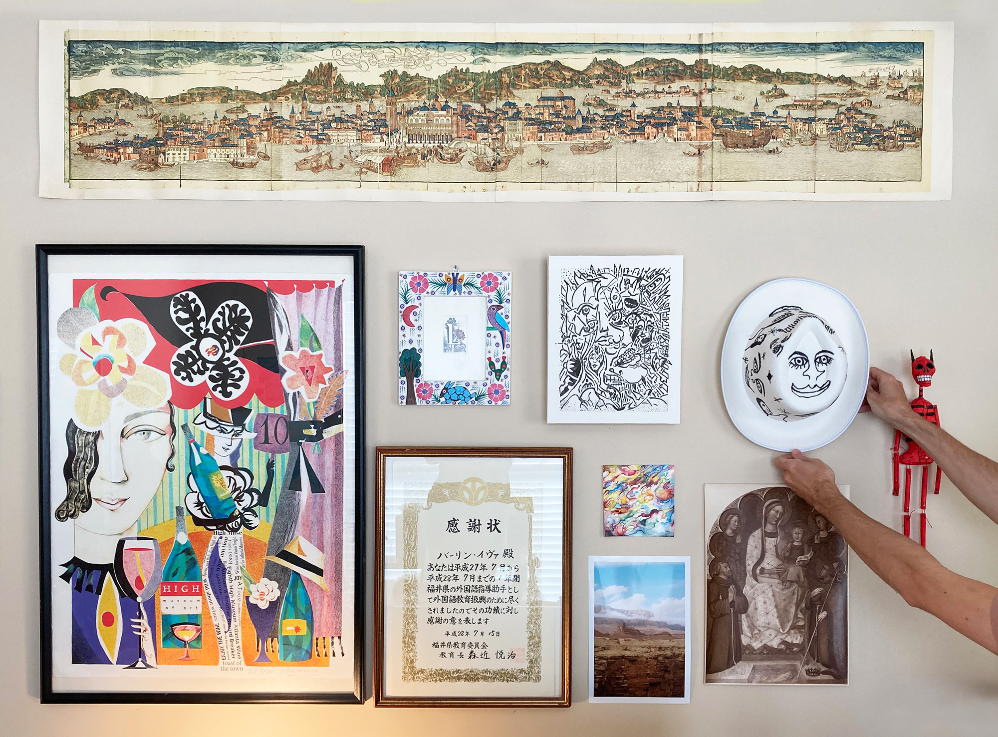 A grouping of artworks and objects, with a pair of hands reaching in from the right side to adjust a hat.