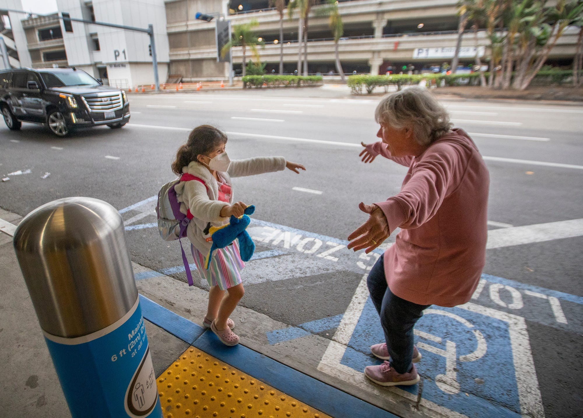 Seven-year-old Jacquie Carney runs to hug her grandma, Donna Vidrine, upon arrival in Los Angeles, California on November 23, 2020.