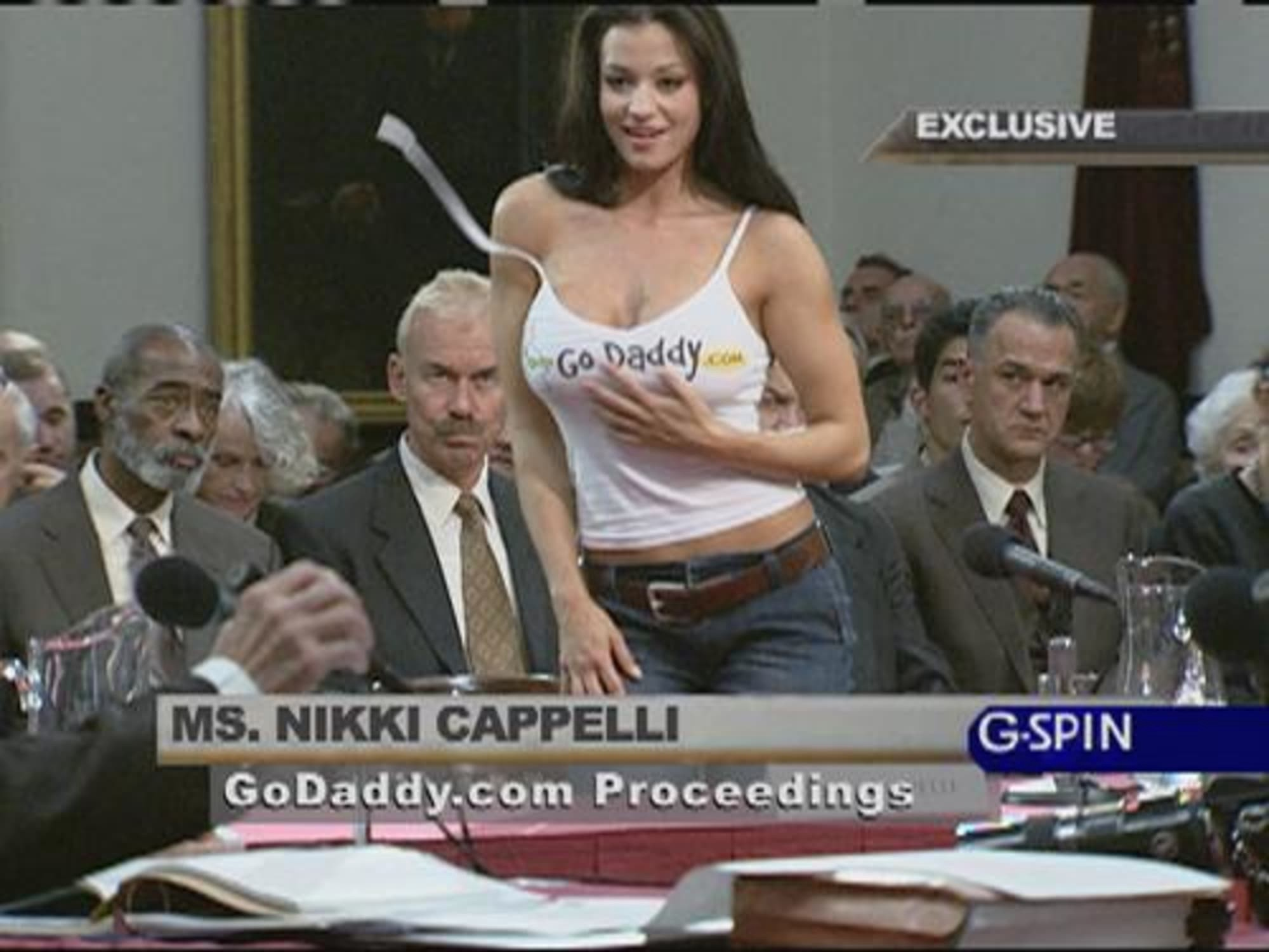 Still from a commercial, featuring a woman with cropped tank top with GoDaddy logo, surrounded by men in a courtroom setting.