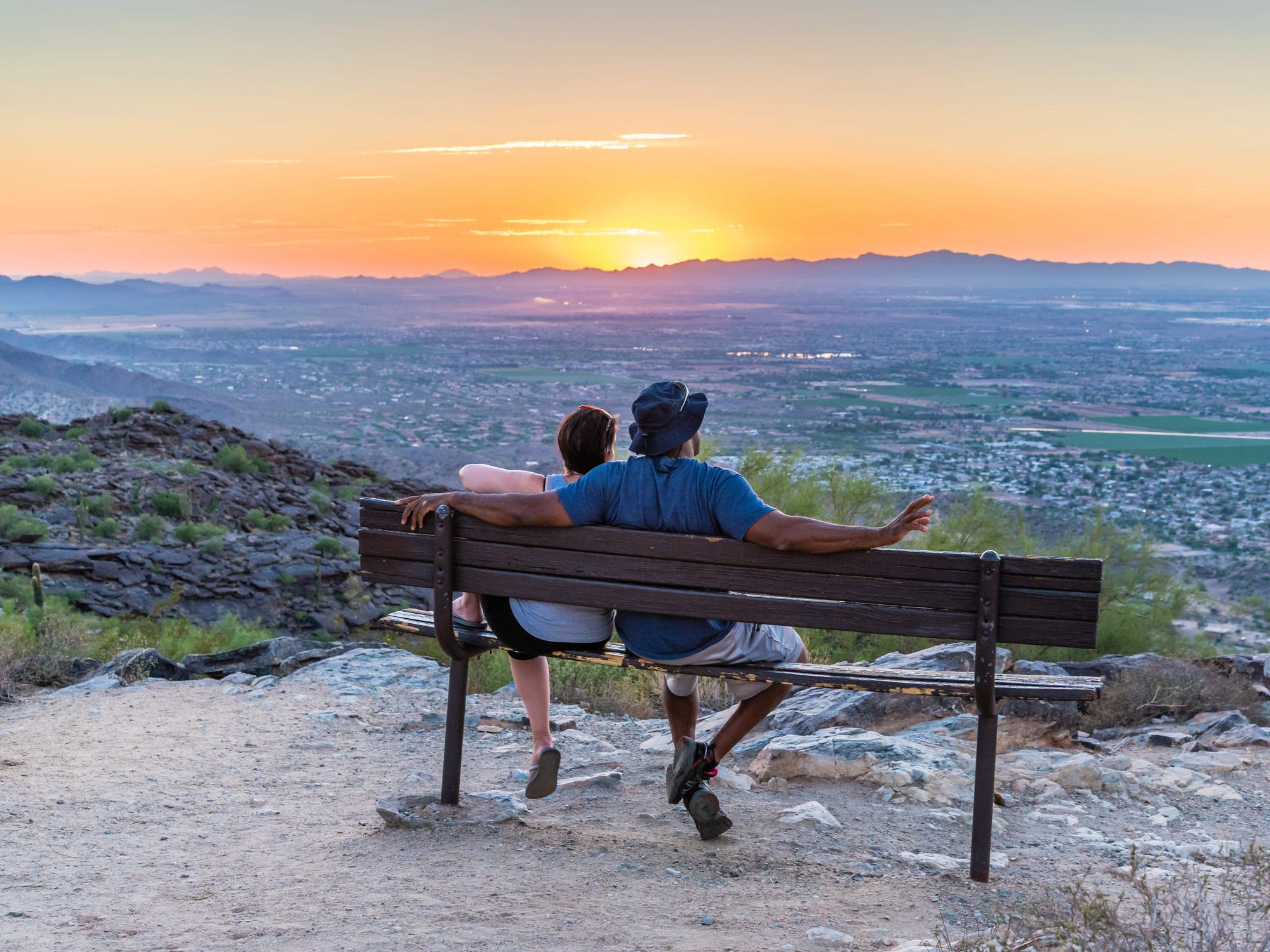 Two people sitting on a bench looking at the sunset.