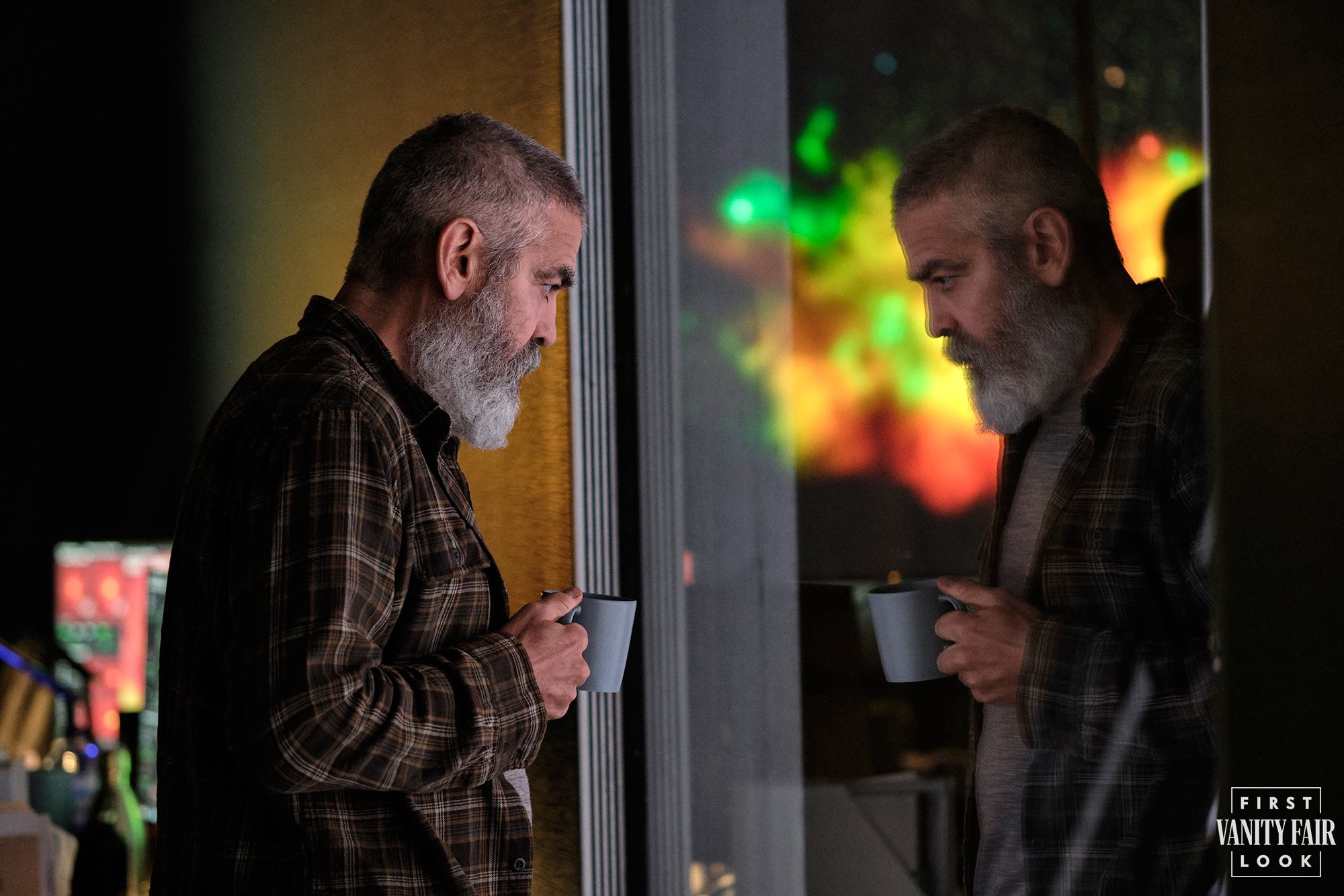 George Clooney, playing his character in The Midnight Sky, looks at his reflection in the mirror.