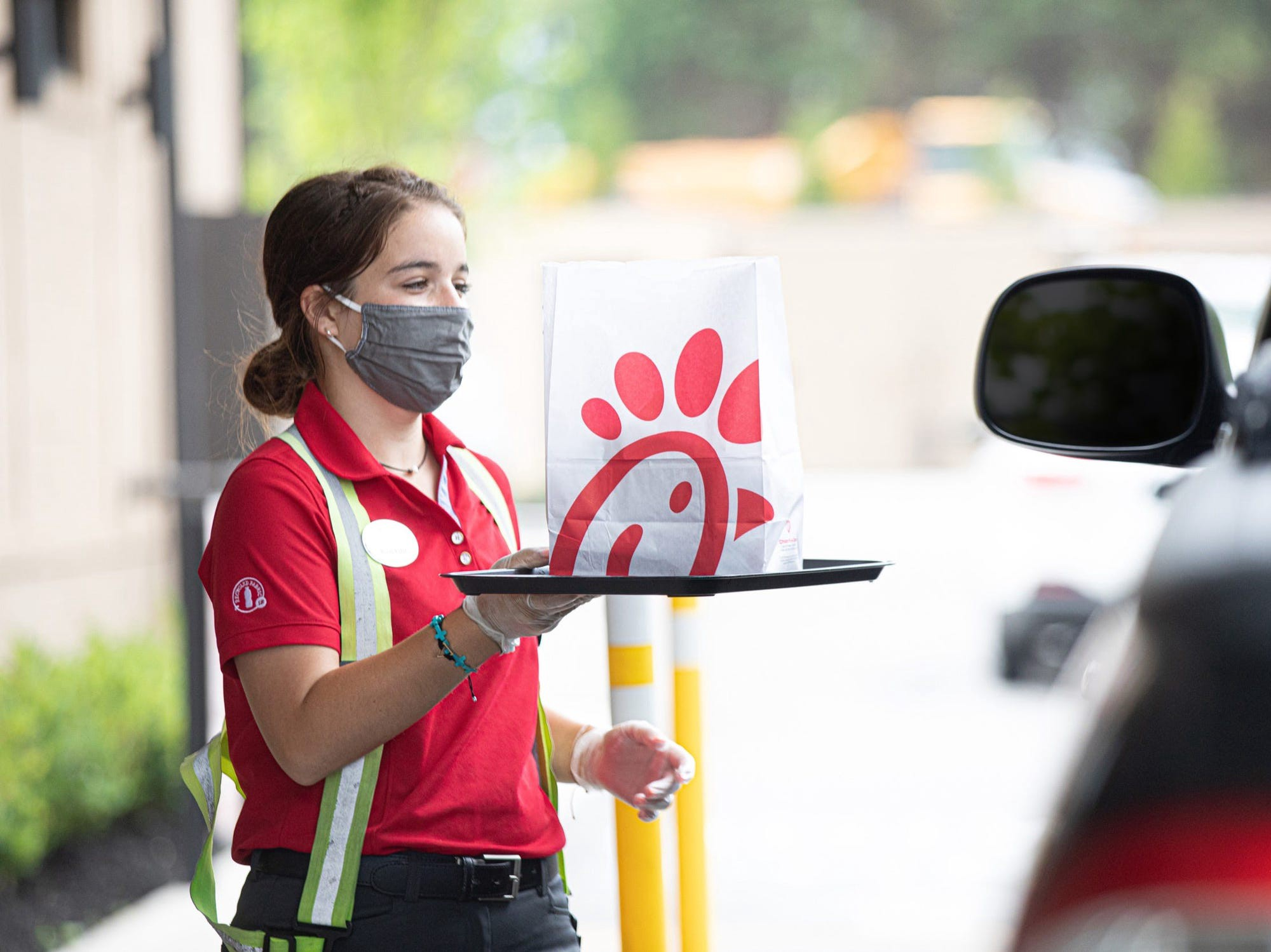A Chick-fil-A employee delivering food to a drive-thru customer.