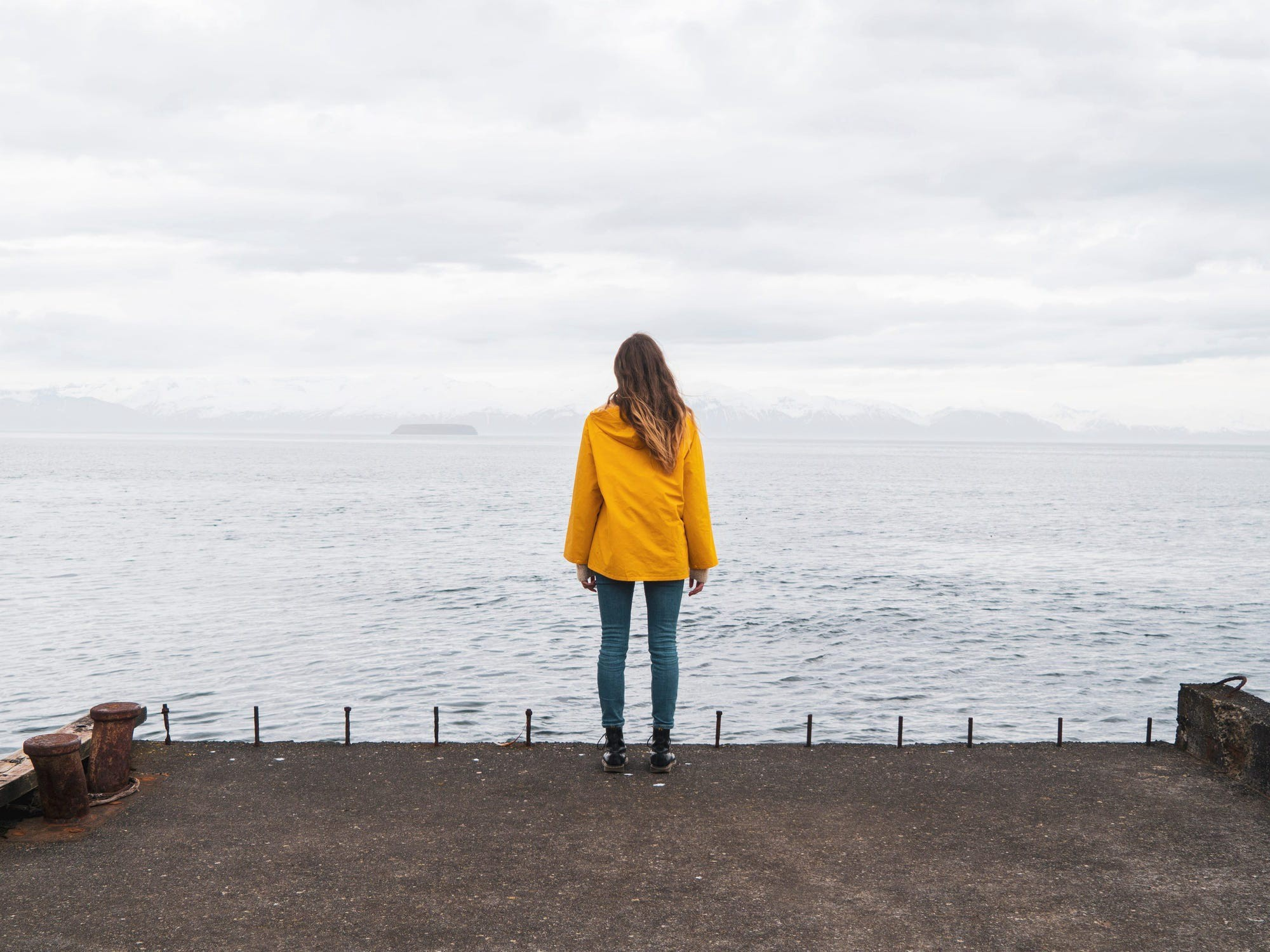 A woman in a yellow coat looking over out into a body of water.