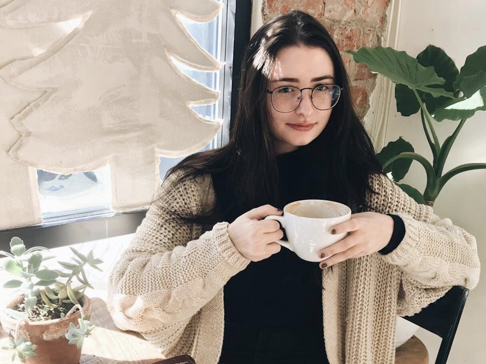 The author holding a cup of coffee.