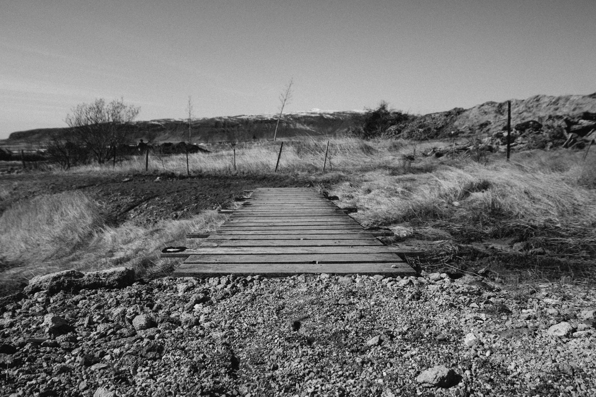 Gravel path leads to worn wooden planks extending into a rocky dry grass landscape without trees