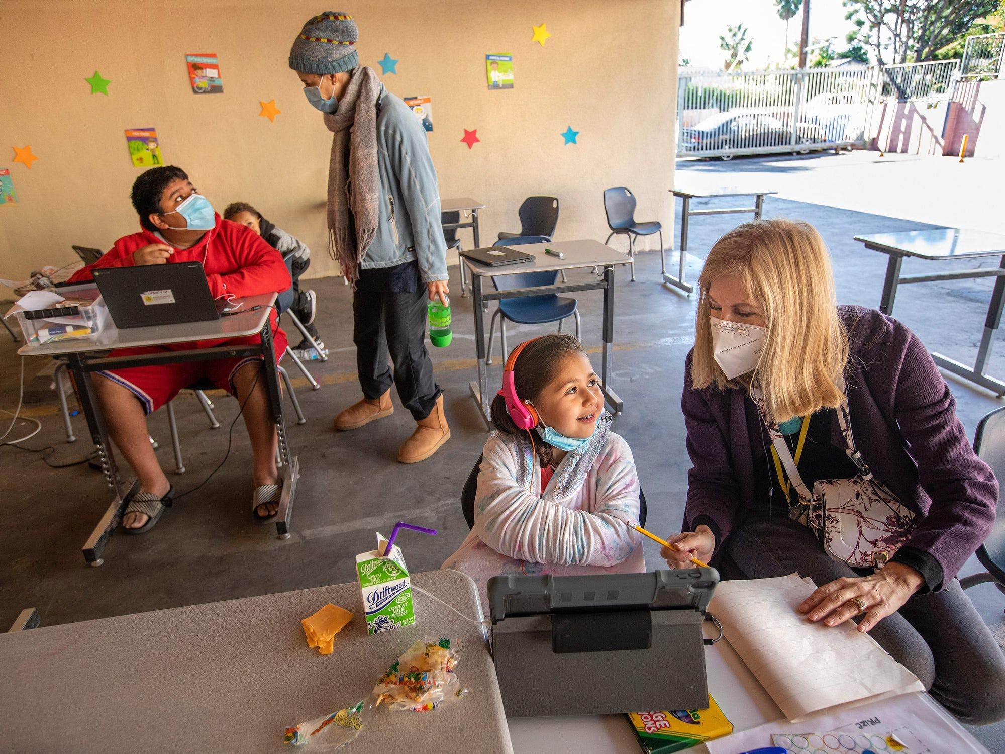 Volunteers help students at a learning pod for homeless children in California.
