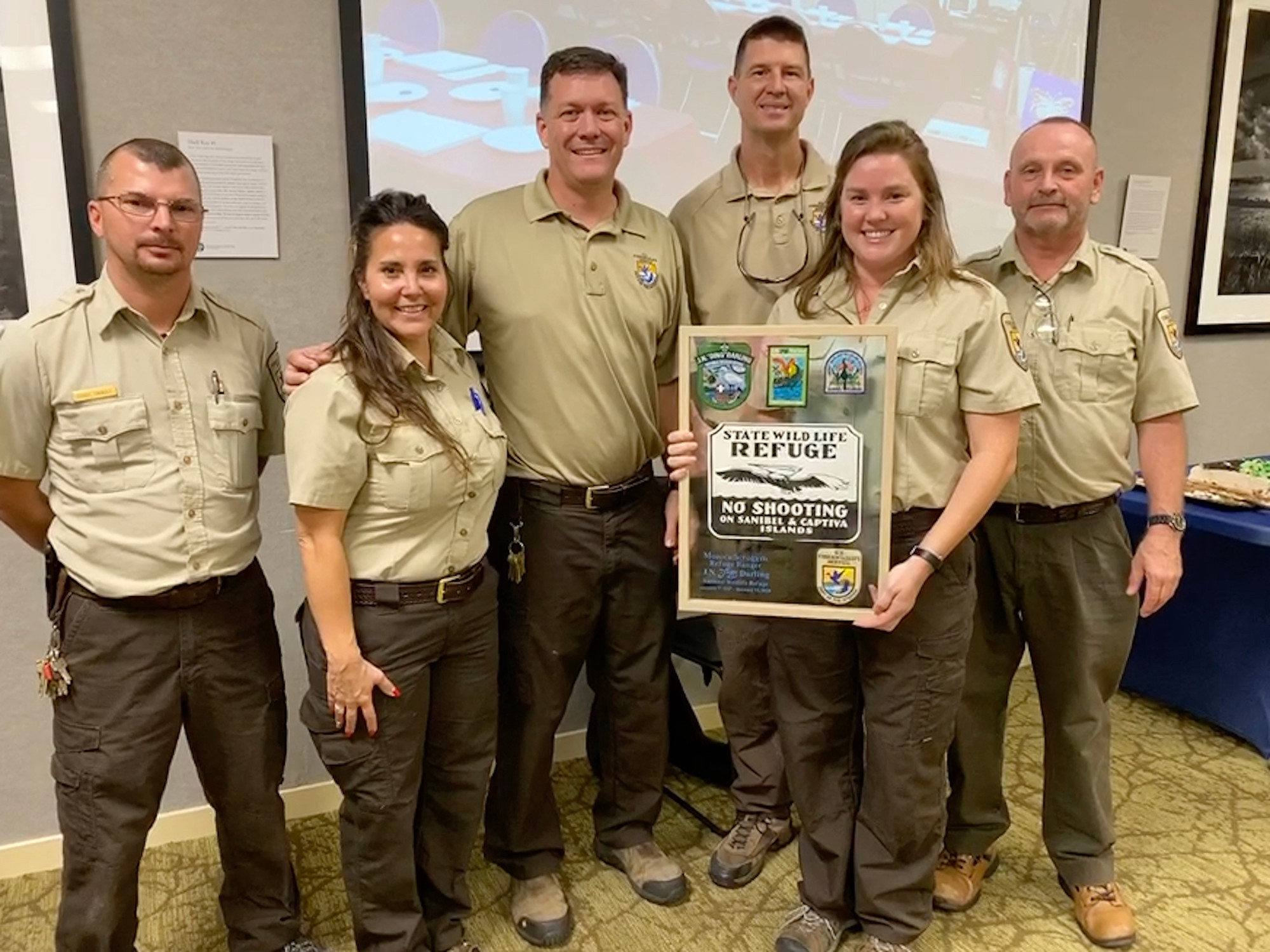"6 people in FWS uniform hold plaque that reads ""State Wildlife Refuge/No Shooting/on Sanibel & Captiva/Islands"" with smaller type and logos"