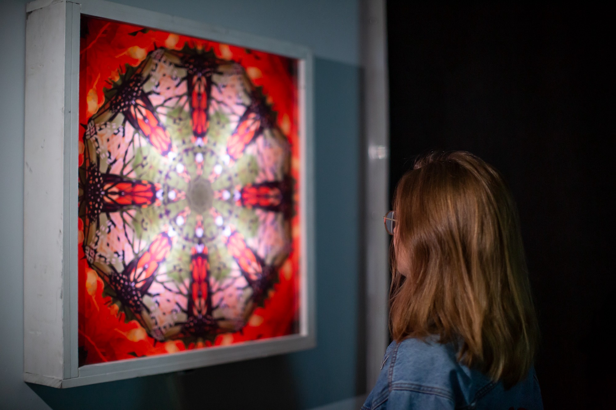 A woman looks at one of Steve's pieces from the Hive series. It's a red square with kaleidoscope-like fractals of a butterfly