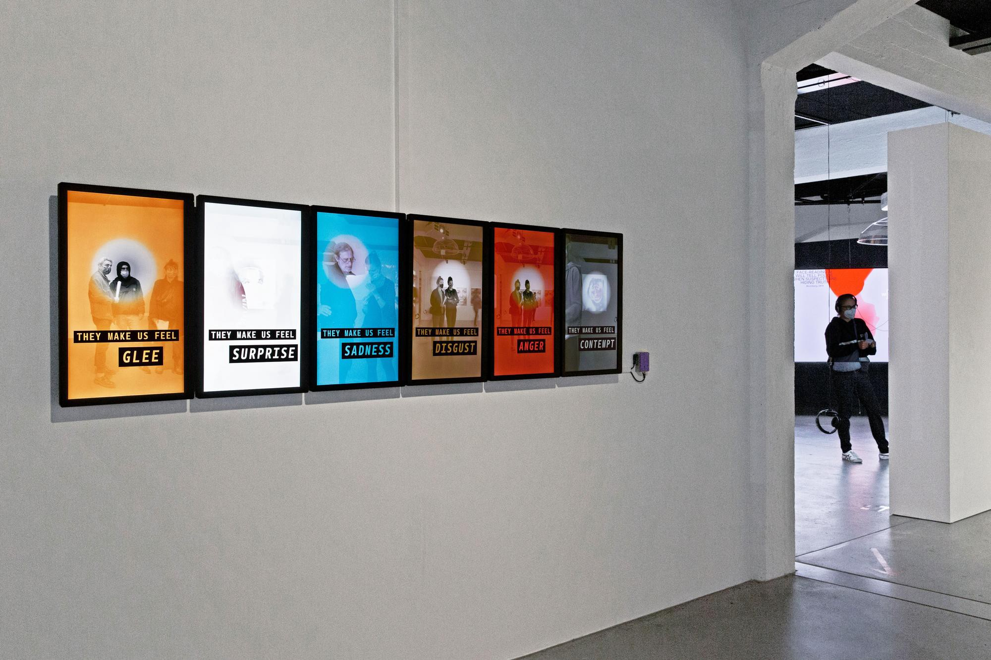 Six adjacent monitors mounted in portrait on a gallery wall, with one photo on each and a circle highlighting a face.